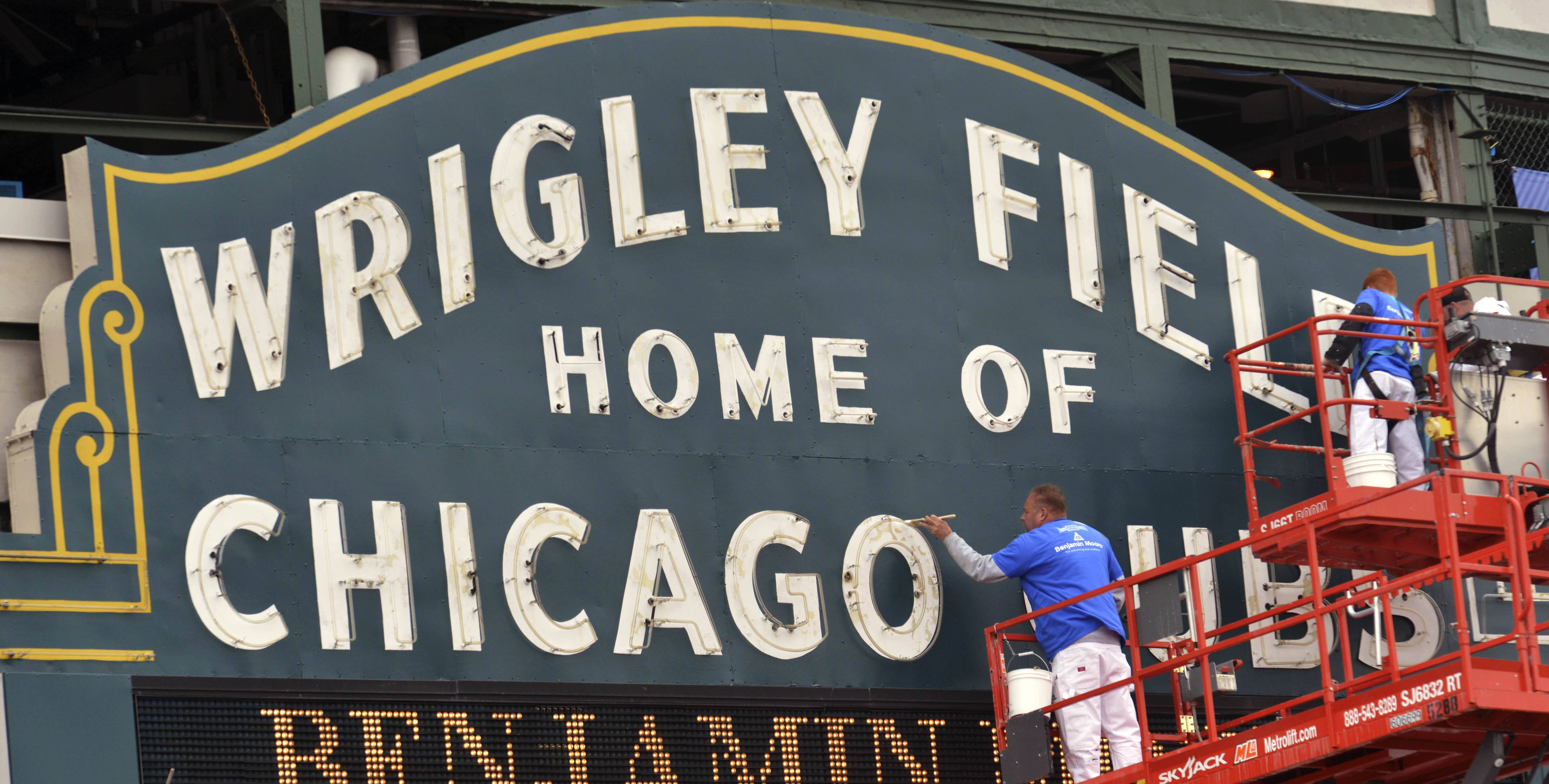 Painters put the finishing touches with green and gold paint on the iconic marquee outside Wrigley Field on Wednesday, May 14, 2014, to match the colors from 1930s as part of the field's anniversary celebration before the Cubs homestand against the Milwaukee Brewers and New York Yankees beginning Friday. (AP Photo/Sun-Times Media, Al Podgorski)  MANDATORY CREDIT, MAGS OUT, NO SALES