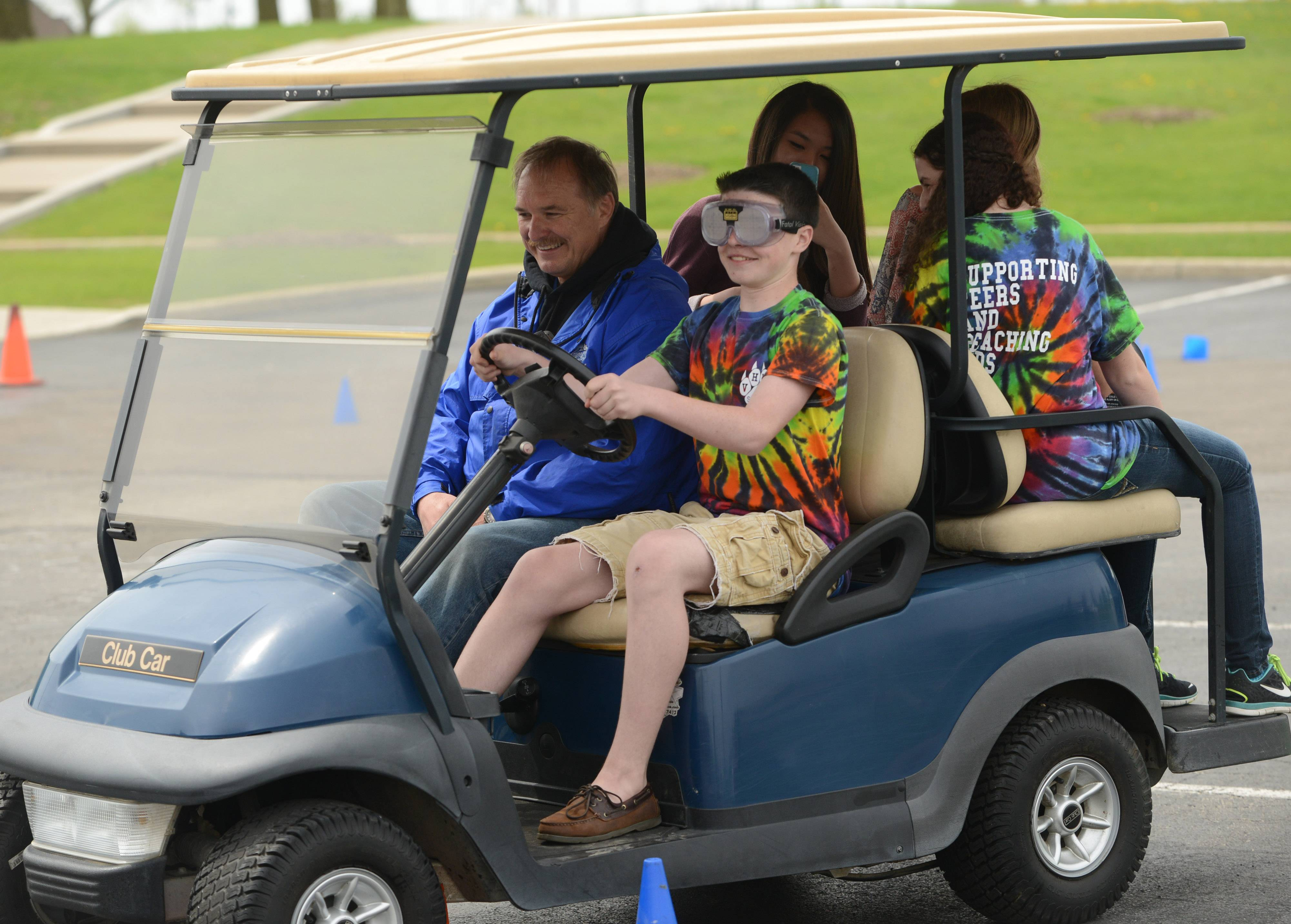 Vernon Hills High School freshman Zak Baumann drives the obstacle course Wednesday wearing special goggles simulating drunken driving. Security guard Al Frank, left, points out various obstacles during the prom week activity.