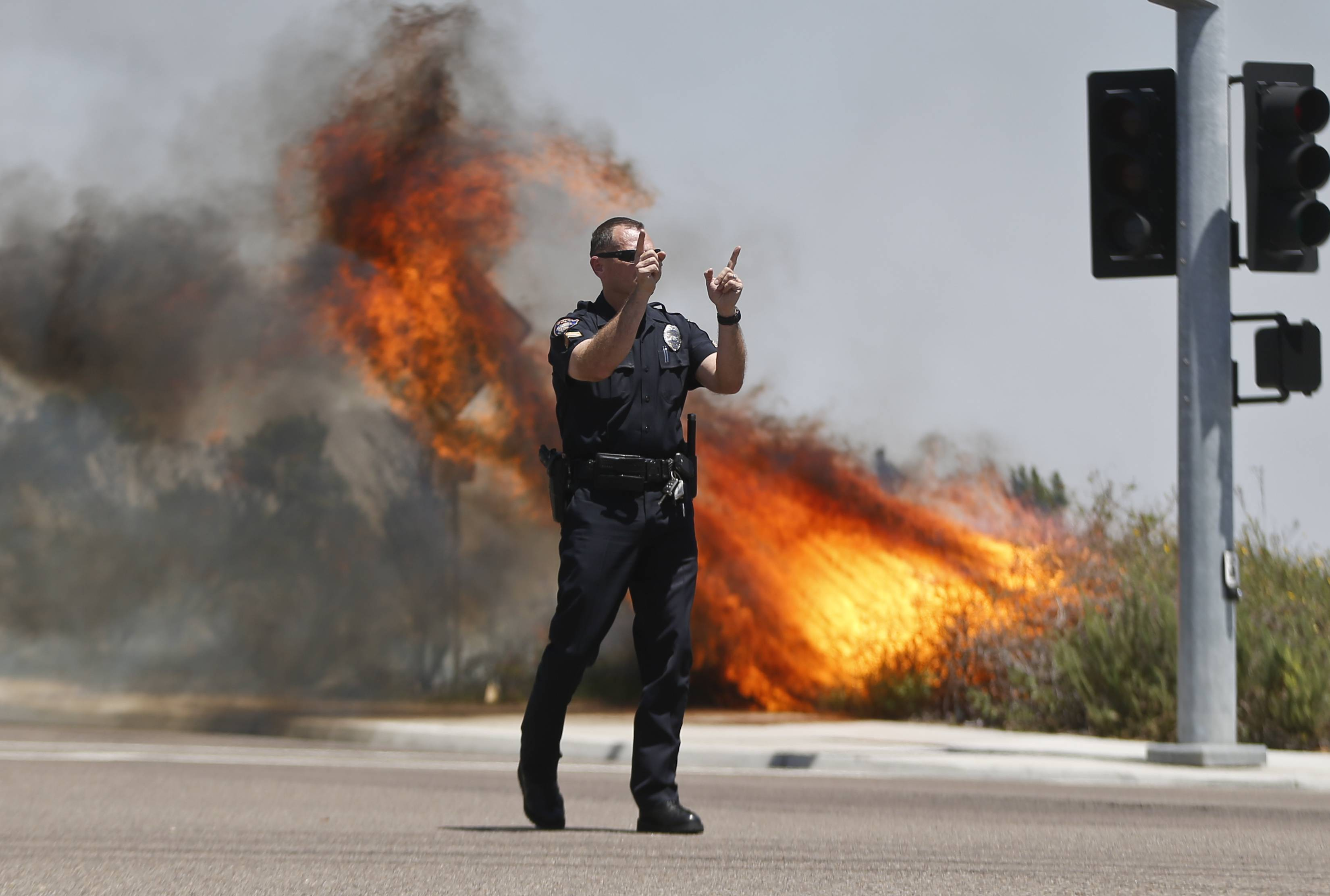 A police officer turns traffic away as flames leap behind him Wednesday in Carlsbad, Calif.