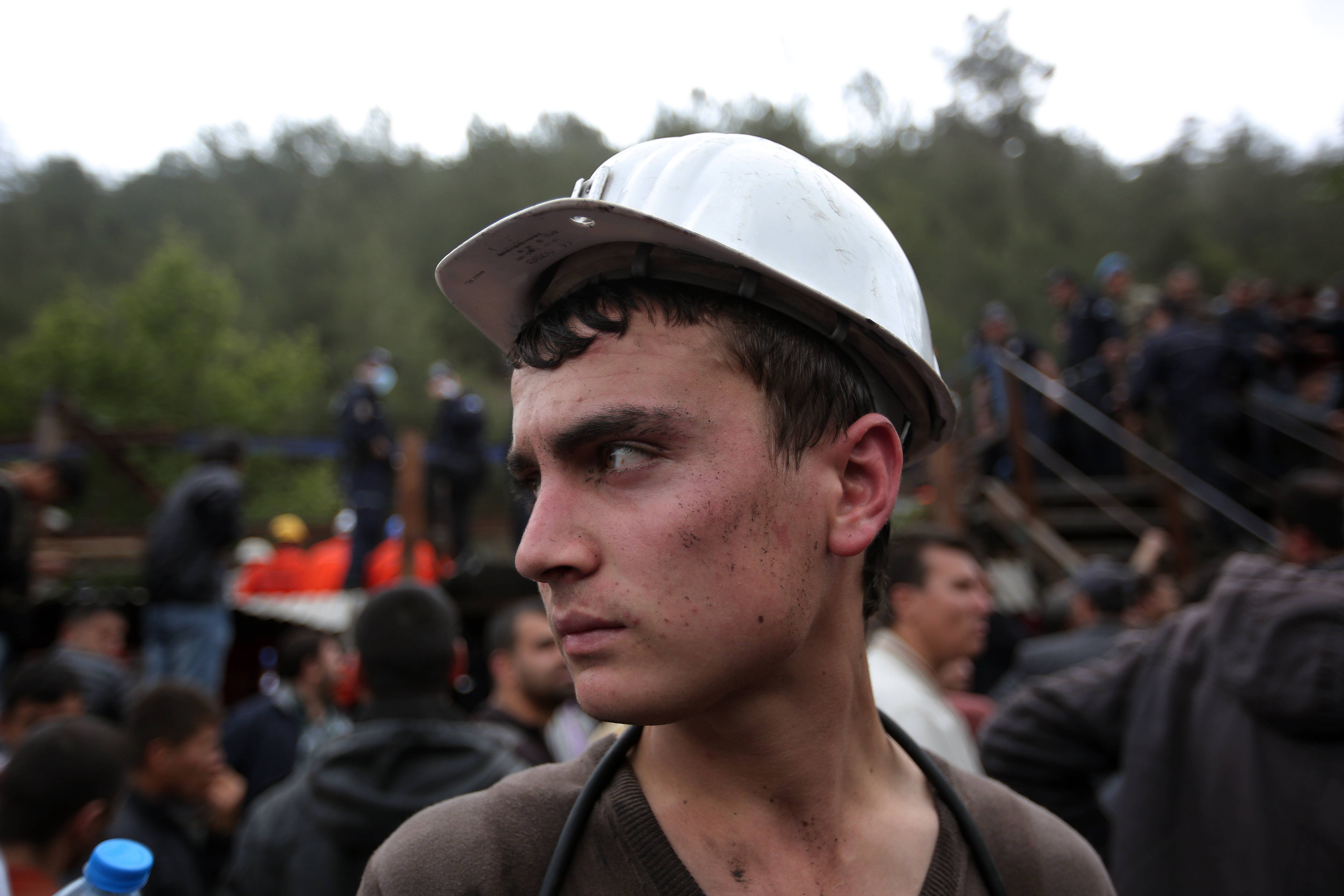 A miner looks on as rescue workers carry the dead body of a miner outside the mine in Soma, western Turkey, Wednesday, May 14, 2014.