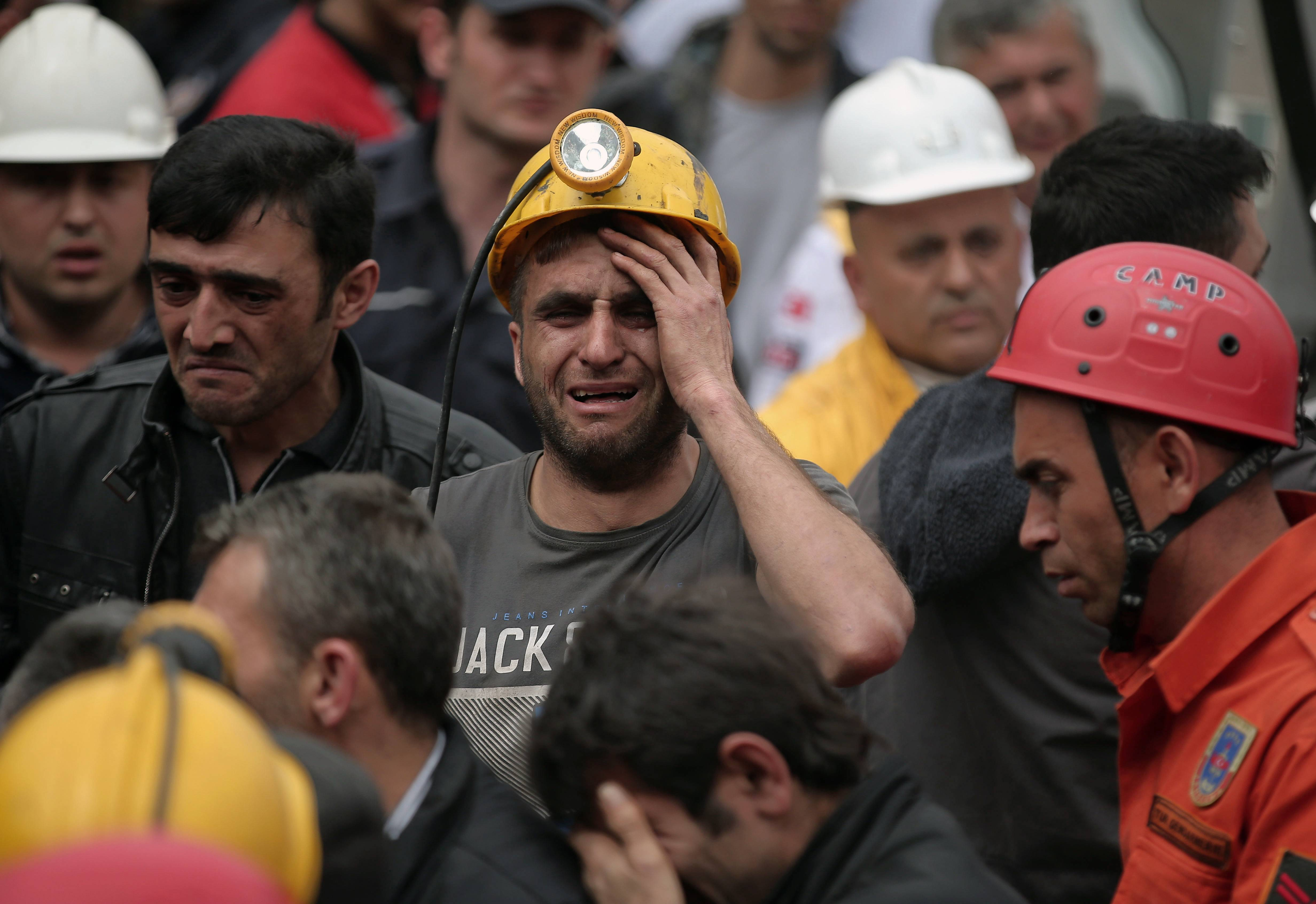 A miner cries as rescue workers carry the dead body of a miner from the mine in Soma, western Turkey, Wednesday, . An explosion and fire at the coal mine killed at least 238 workers, authorities said, in one of the worst mining disasters in Turkish history.