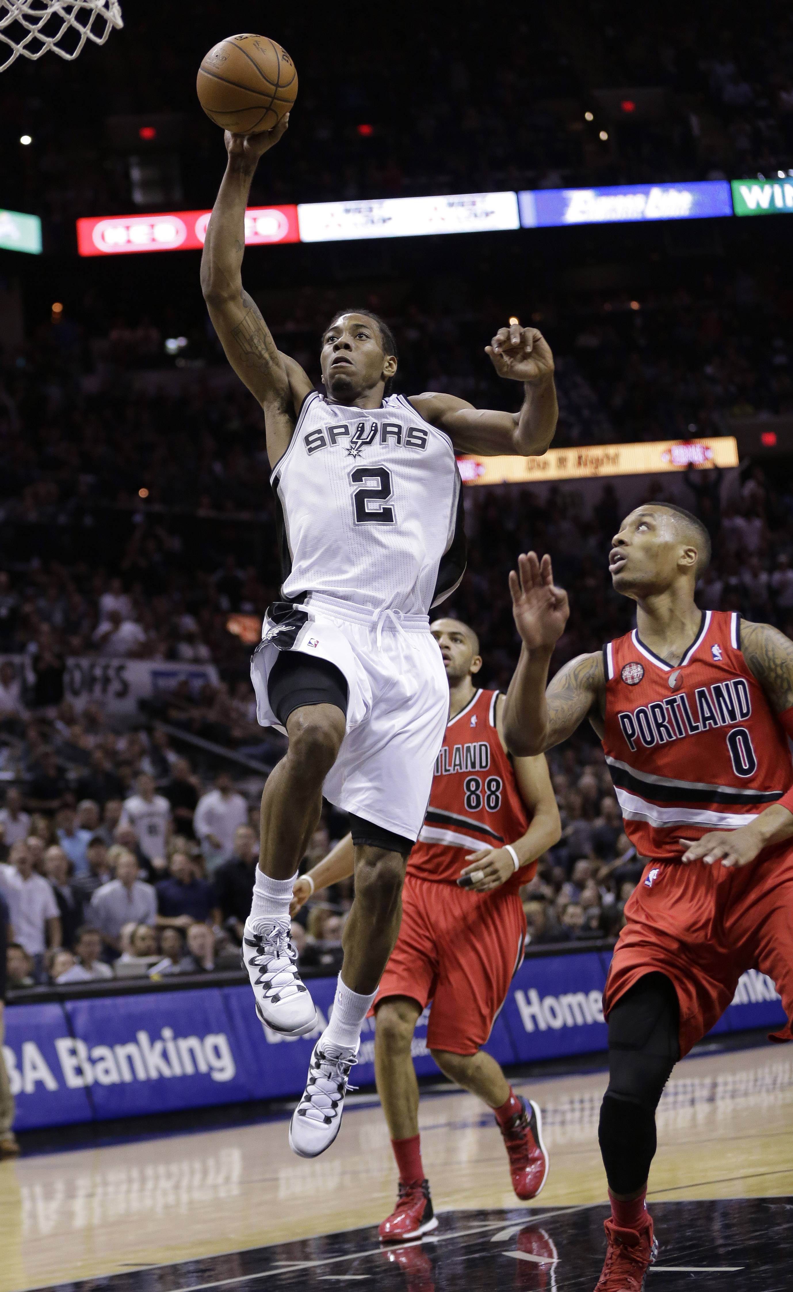 San Antonio Spurs' Kawhi Leonard (2) scores in front of Portland Trail Blazers' Damian Lillard (0) during the second half of Game 5 of a Western Conference semifinal NBA basketball playoff series, Wednesday, May 14, 2014, in San Antonio.