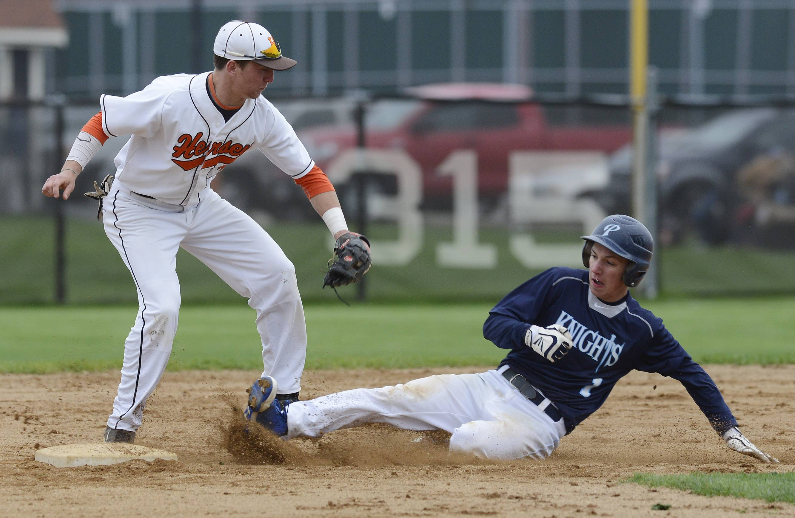 Prospect's Tyler Damasky slides safely under the tag of Hersey's Jack Warner as he steals second base during Wednesday's game in Arlington Heights.