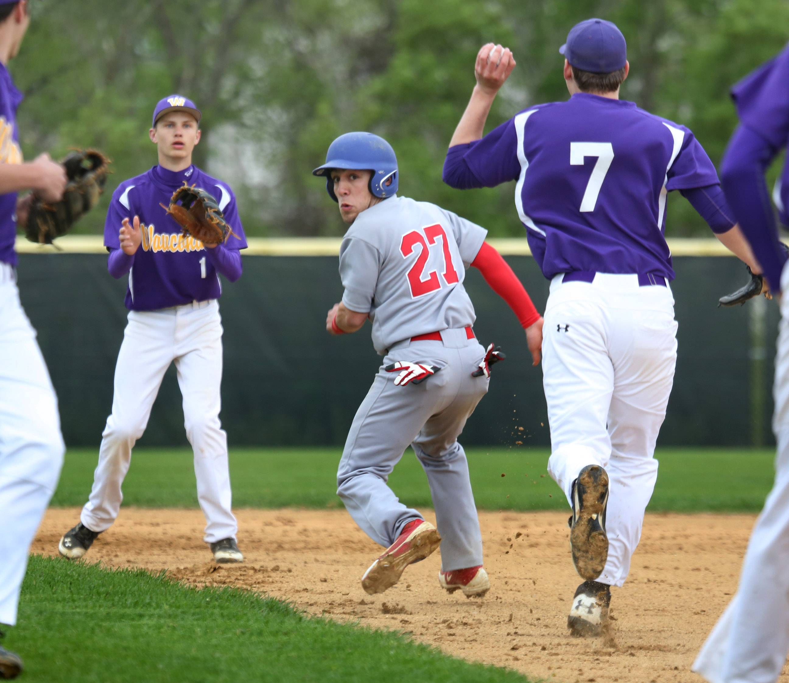 Lakes' Justin Corona gets caught in a rundown between first and second as Wauconda's Collin Shrader, left, and Kyle Harmon chase hm down.
