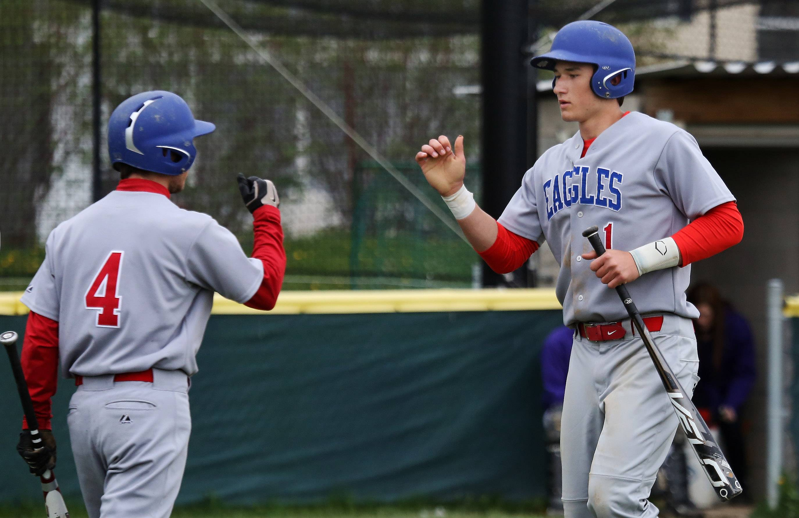 Lakes' Ethan Sage, right, is congratulated by Brad Borzick after scoring the first run in the second inning on the Eagles' NSC Prairie game at Wauconda.