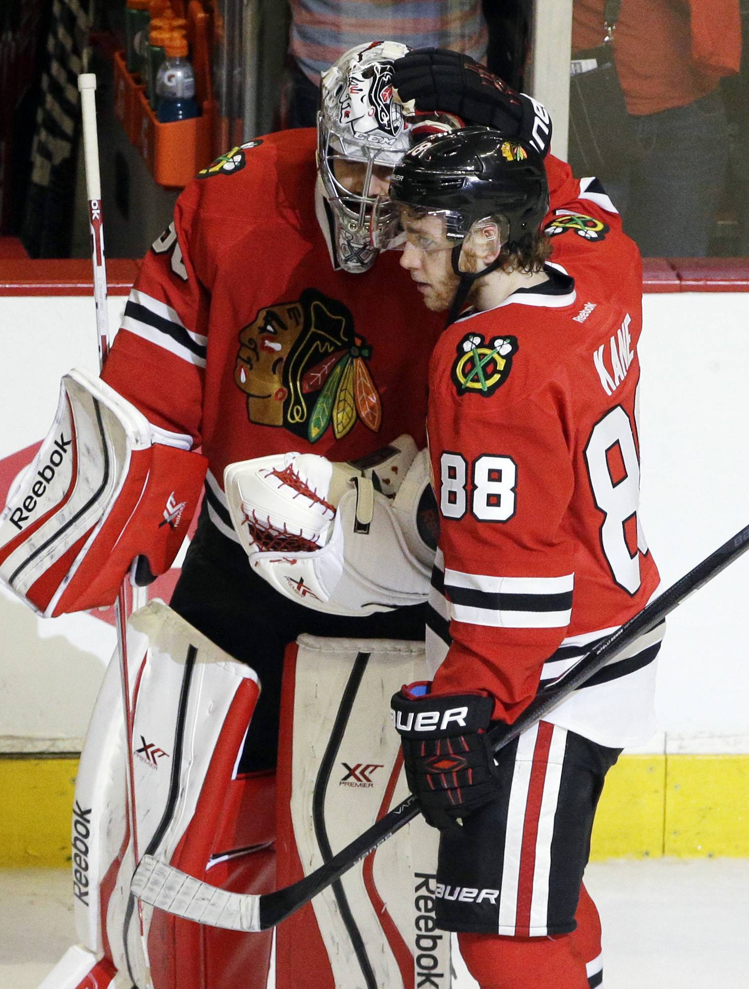 Blackhawks goalie Corey Crawford celebrates with Patrick Kane after Sunday's Game 5 victory over the Wild. Both have done more than their share to get the Hawks into the Western Conference finals.