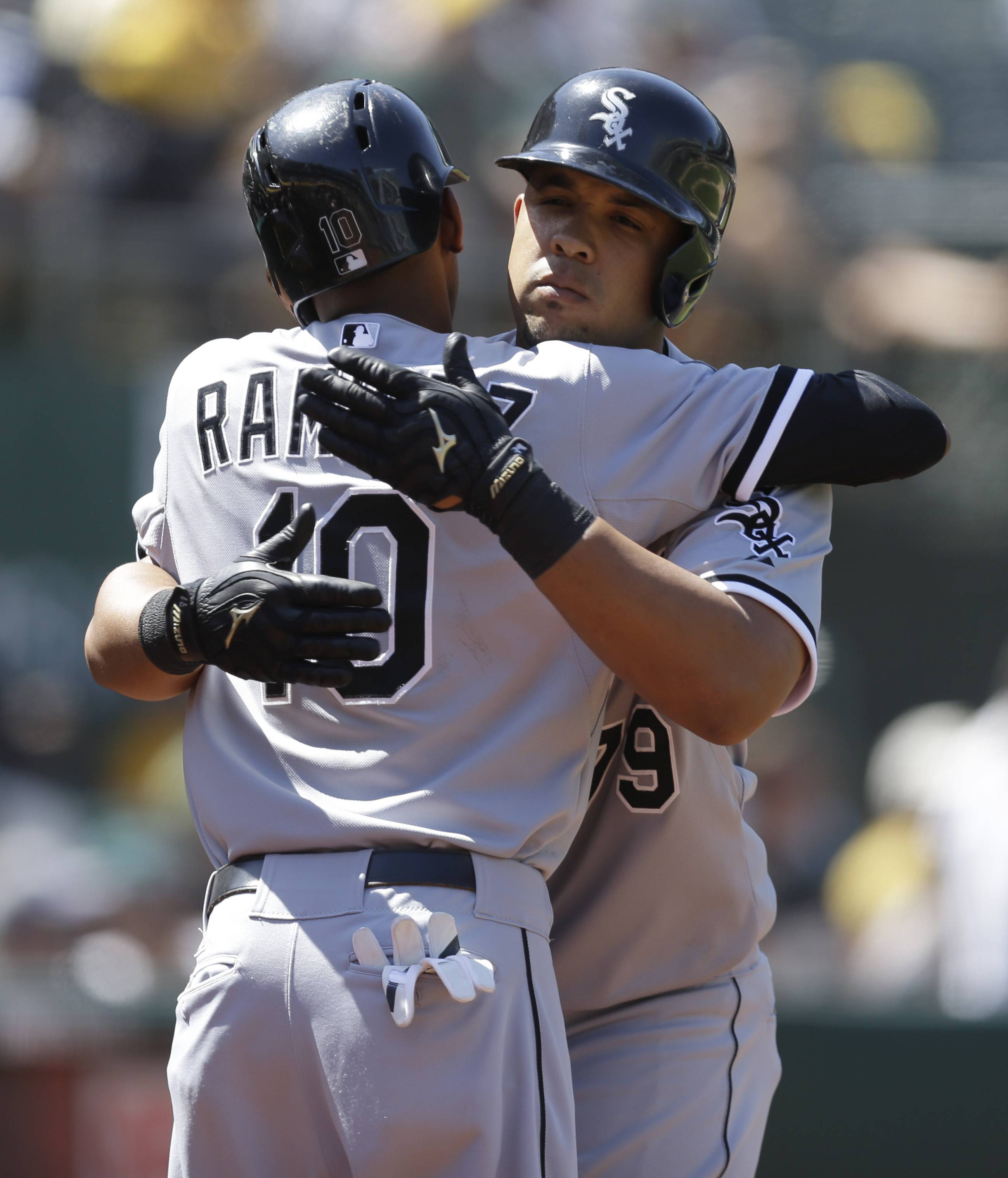 Chicago White Sox's Jose Abreu, right, is embraced by Alexei Ramirez (10) after Abreu hit a three-run home run off Oakland Athletics' Luke Gregerson in the eighth inning of a baseball game Wednesday, May 14, 2014, in Oakland, Calif.