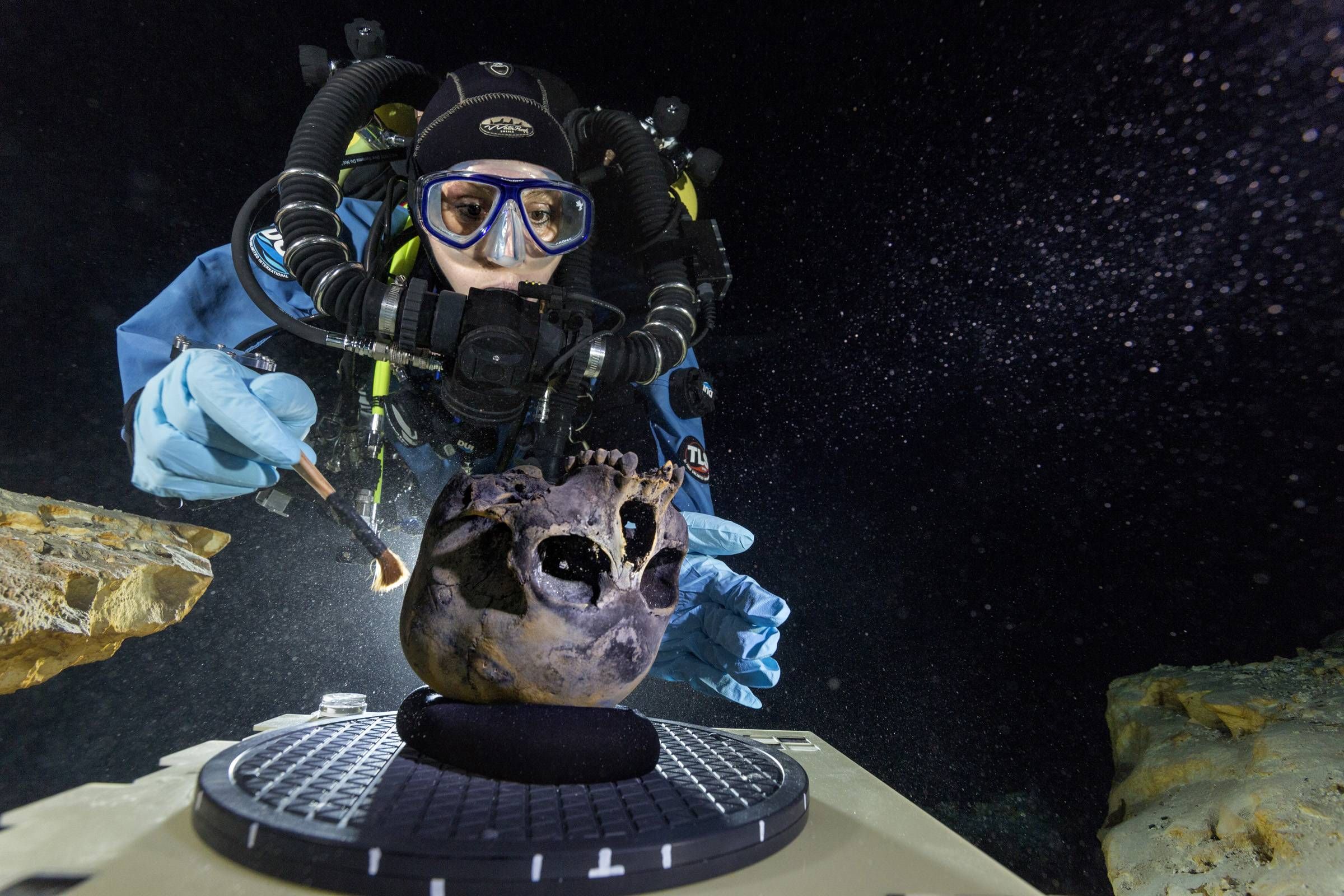 Diver Susan Bird, working at the bottom of Hoyo Negro, a large dome-shaped underwater cave in Mexico's Yucatan Peninsula, brushes a human skull found at the site while her team members take detailed photographs.