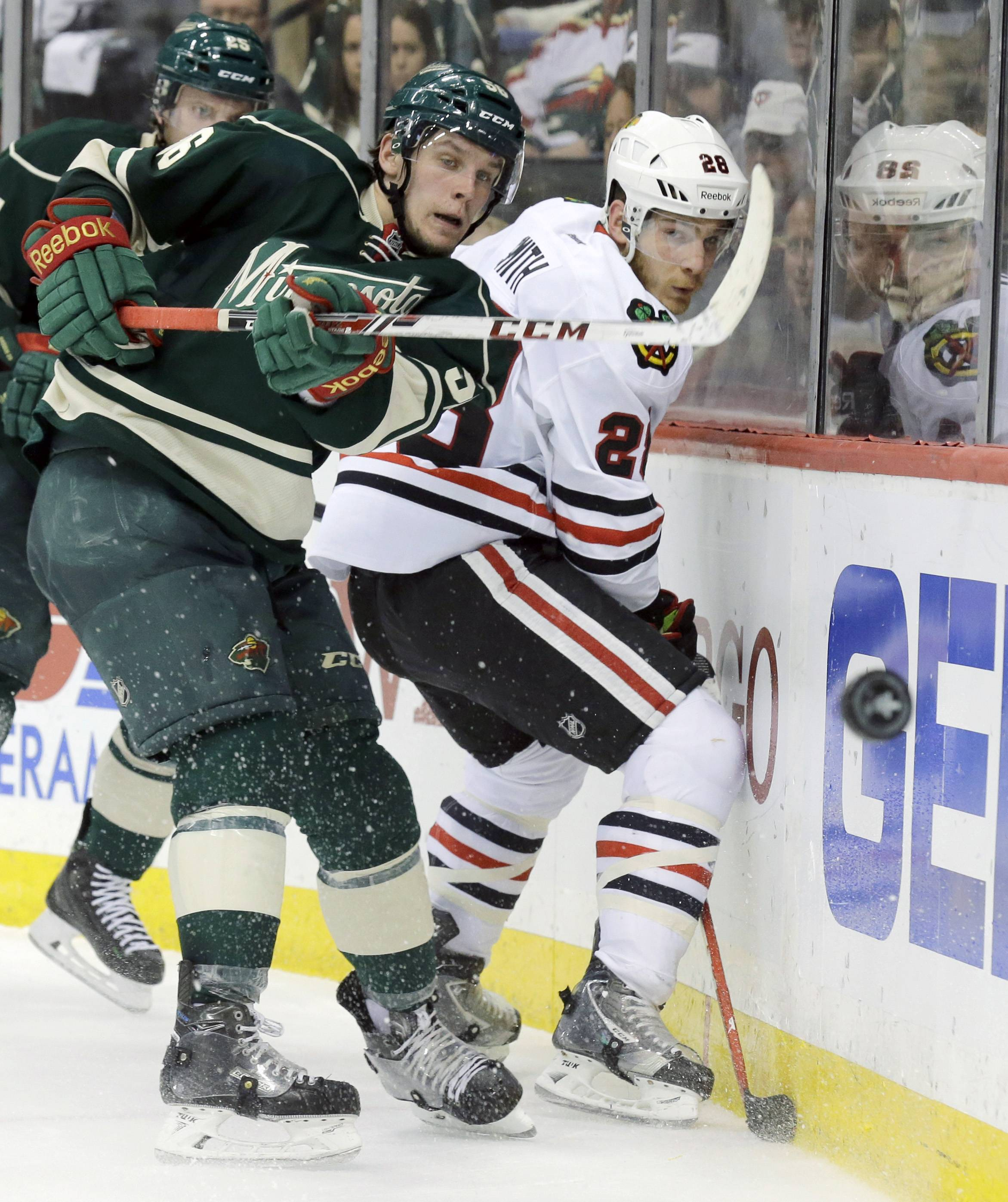 Minnesota Wild left wing Erik Haula, left, of Finland, and Blackhawks forward Ben Smith (28) chase the puck during the second period of Game 6. The Blackhawks won 2-1 in overtime.