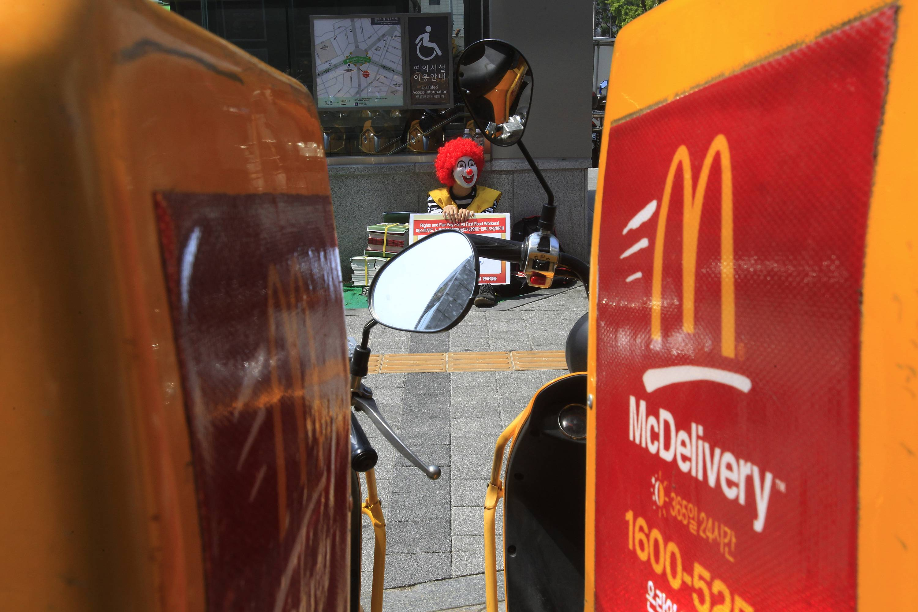A protester dressed as Ronald McDonald sits on the street before a rally to demand higher wages for fast-food workers outside a McDonald restaurant in Seoul, South Korea Thursday.