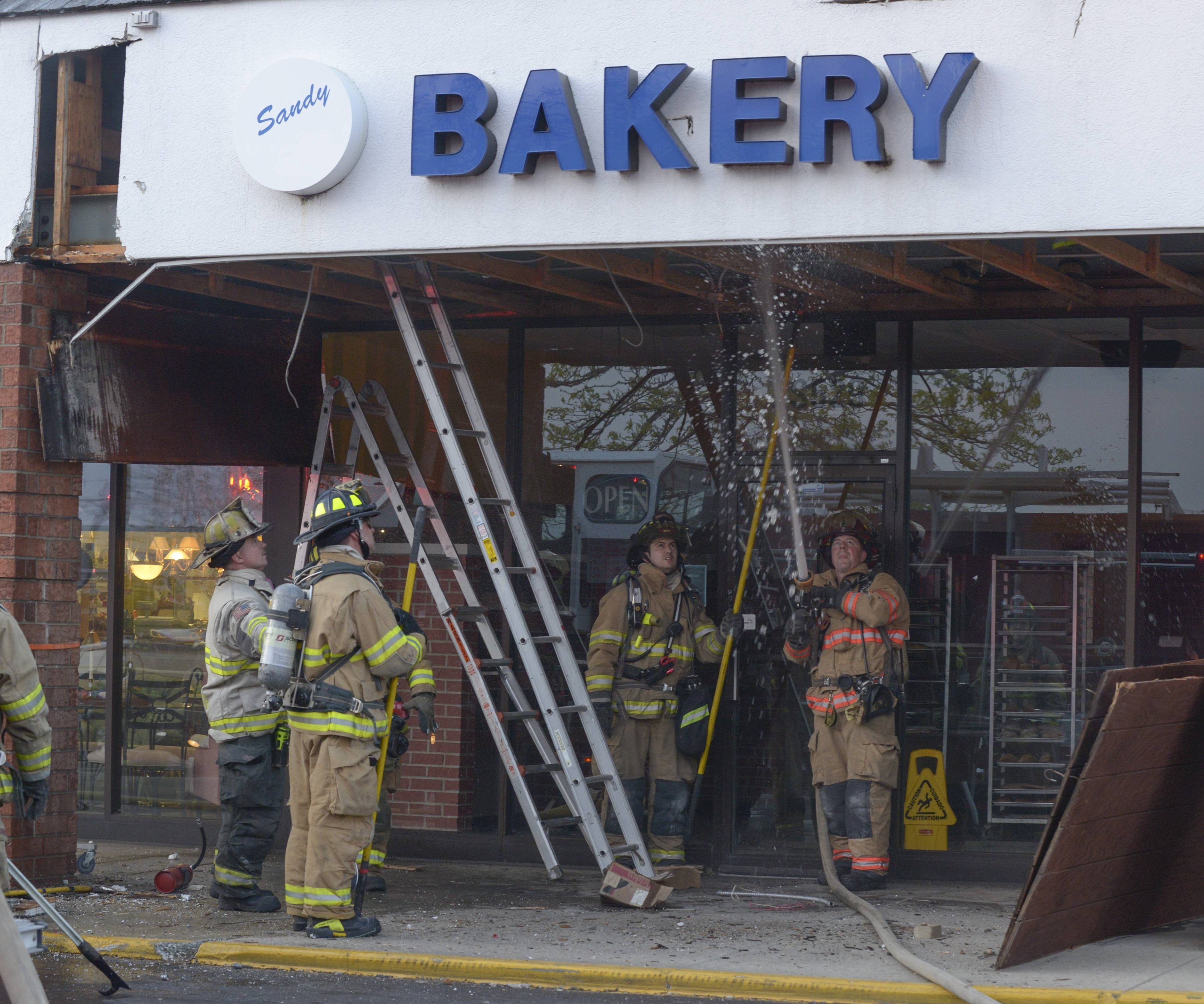 Warrenville firefighters check the rafters of the overhang in front of Sandy's Bakery at the intersection of Route 59 and Batavia Roads in Warrenville, Thursday evening.