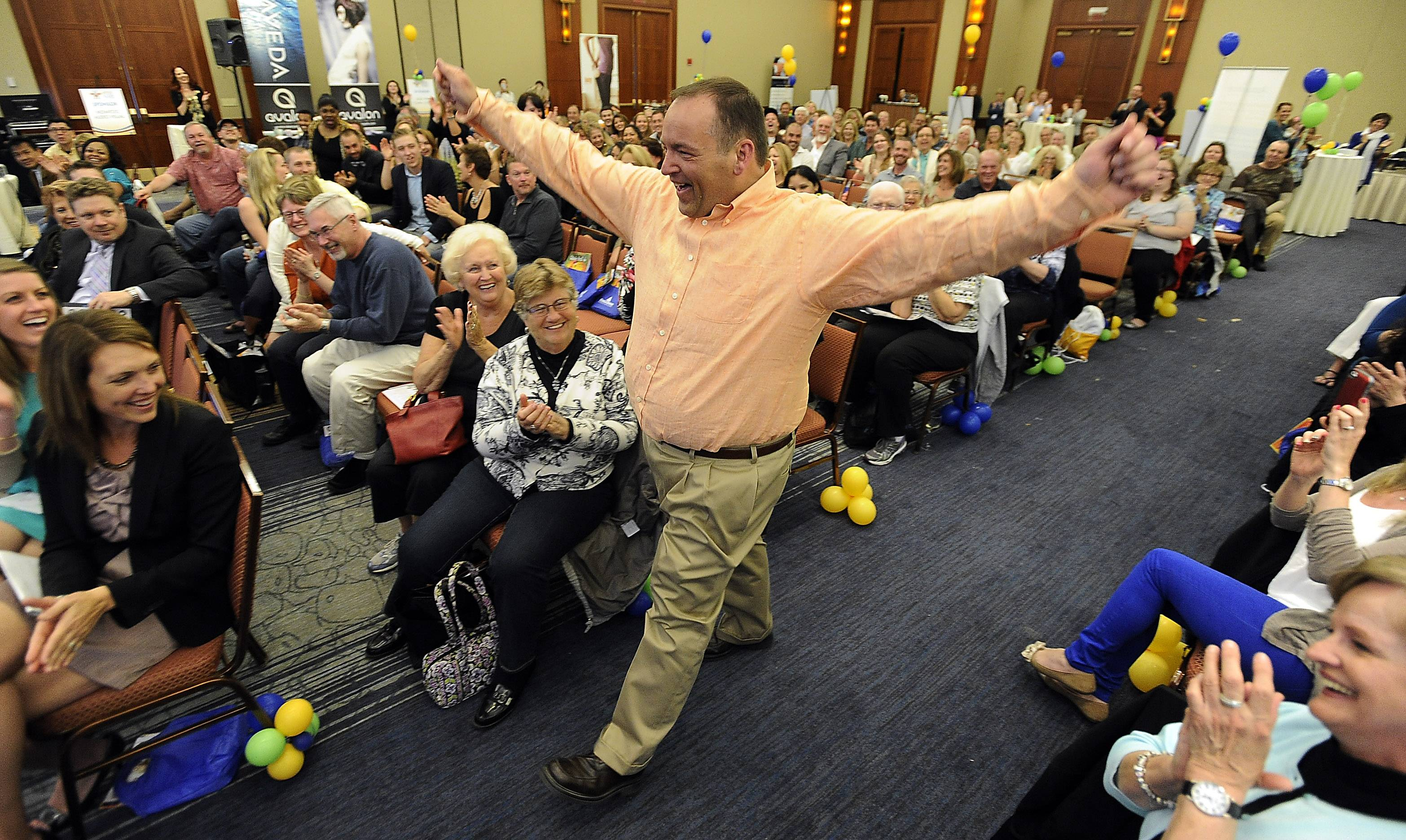 John Bohanek of South Elgin is full of energy as he is introduced to the sold-out crowd at the Daily Herald's 2014 Fittest Loser Challenge ceremony in Itasca Thursday. Bohanek won the challenge after losing 87 pounds in 12 weeks.