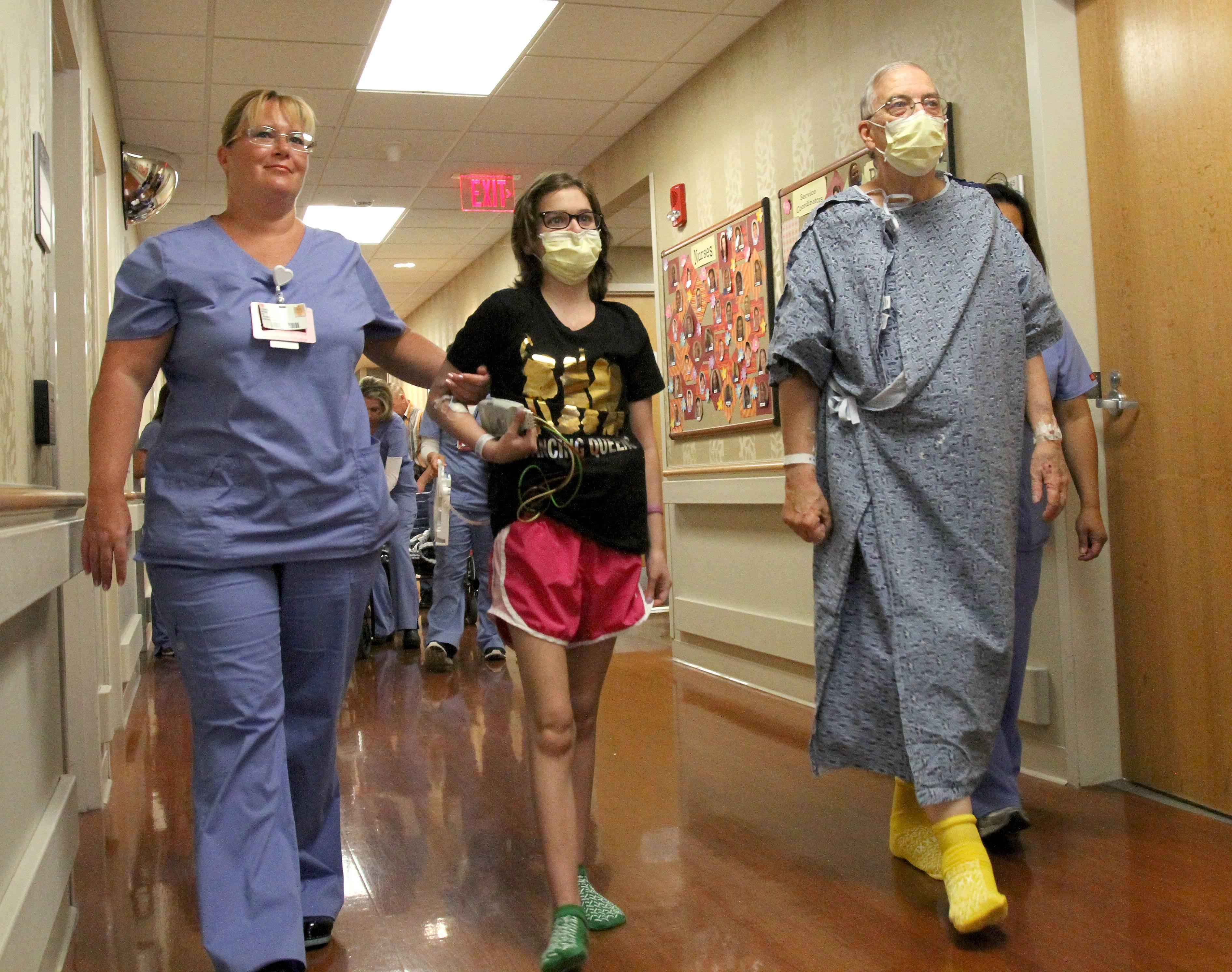 Nurse Theresa Weiss, left, walks Julie D'Agostino of Elmhurst and Robert Senander of Winfield down the hall at Loyola University Medical Center in Maywood. They both had lung transplants and received their lungs from the same donor.