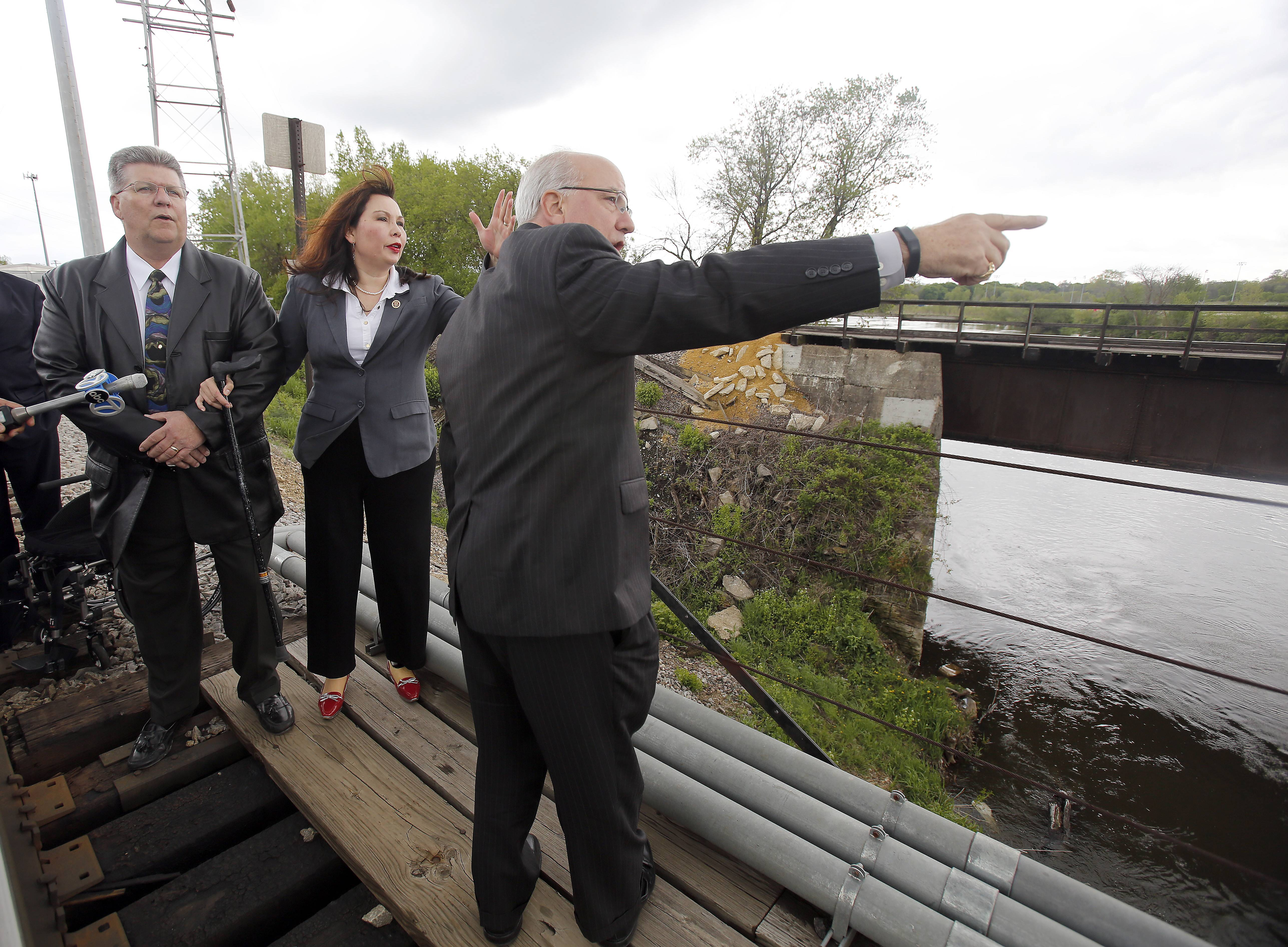 Bill Dorris, board chairman for the National Railroad Construction and Maintenance Association and U.S. Rep. Tammy Duckworth listen as Metra Executive Director/CEO Don Orseno makes a point Thursday near a single-track bridge in Elgin.