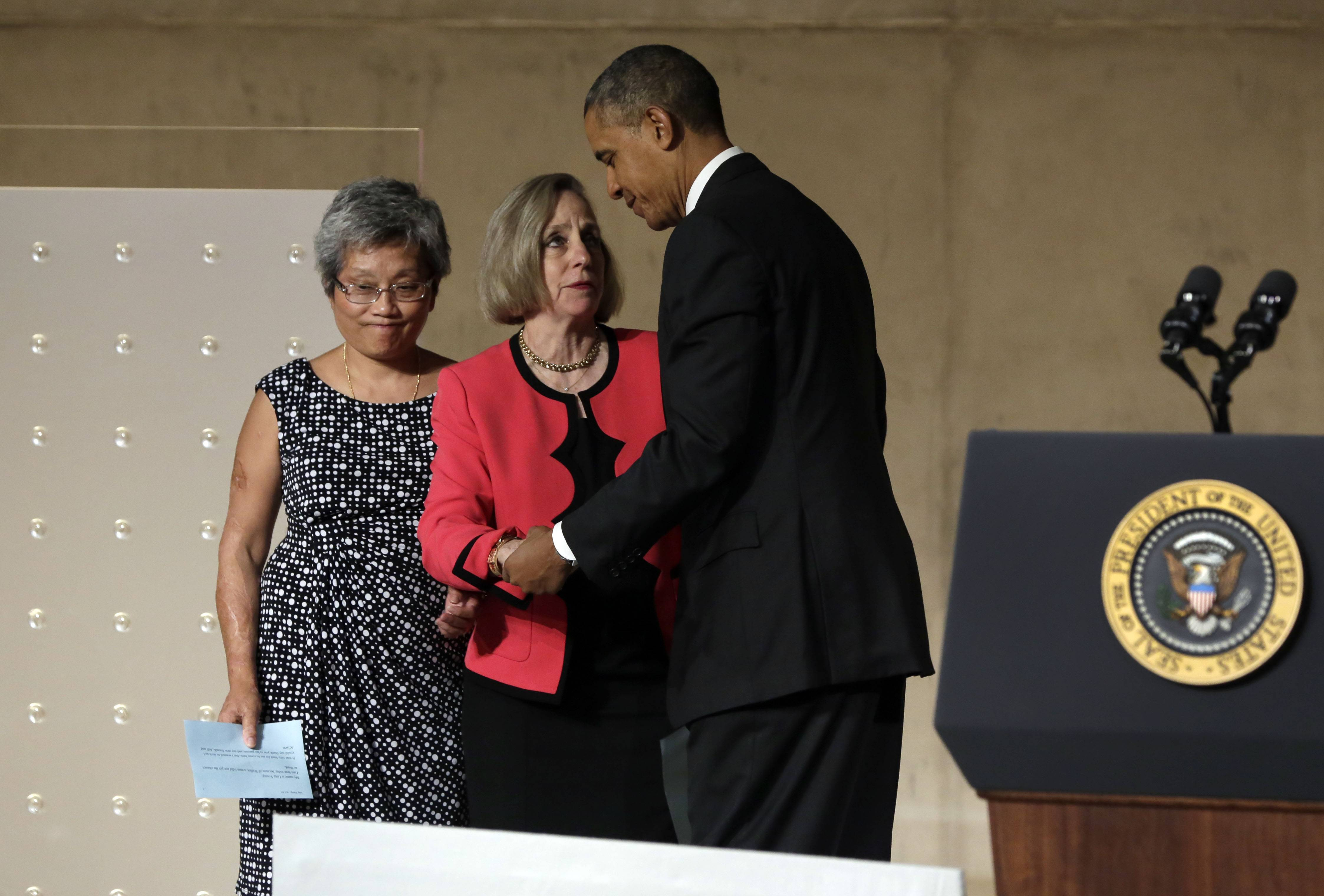 President Barack Obama talks with Ling Young, left, and Alison Crowther before their remarks during the dedication ceremony in Foundation Hall. Young was working on the 86th floor of the South Tower and was one of 12 people who escaped the sky lobby after Flight 175 struck the World Trade Center. Crowther is the mother of Welles Crowther who was killed on September 11 while assisting in the evacuation efforts in the South Tower.
