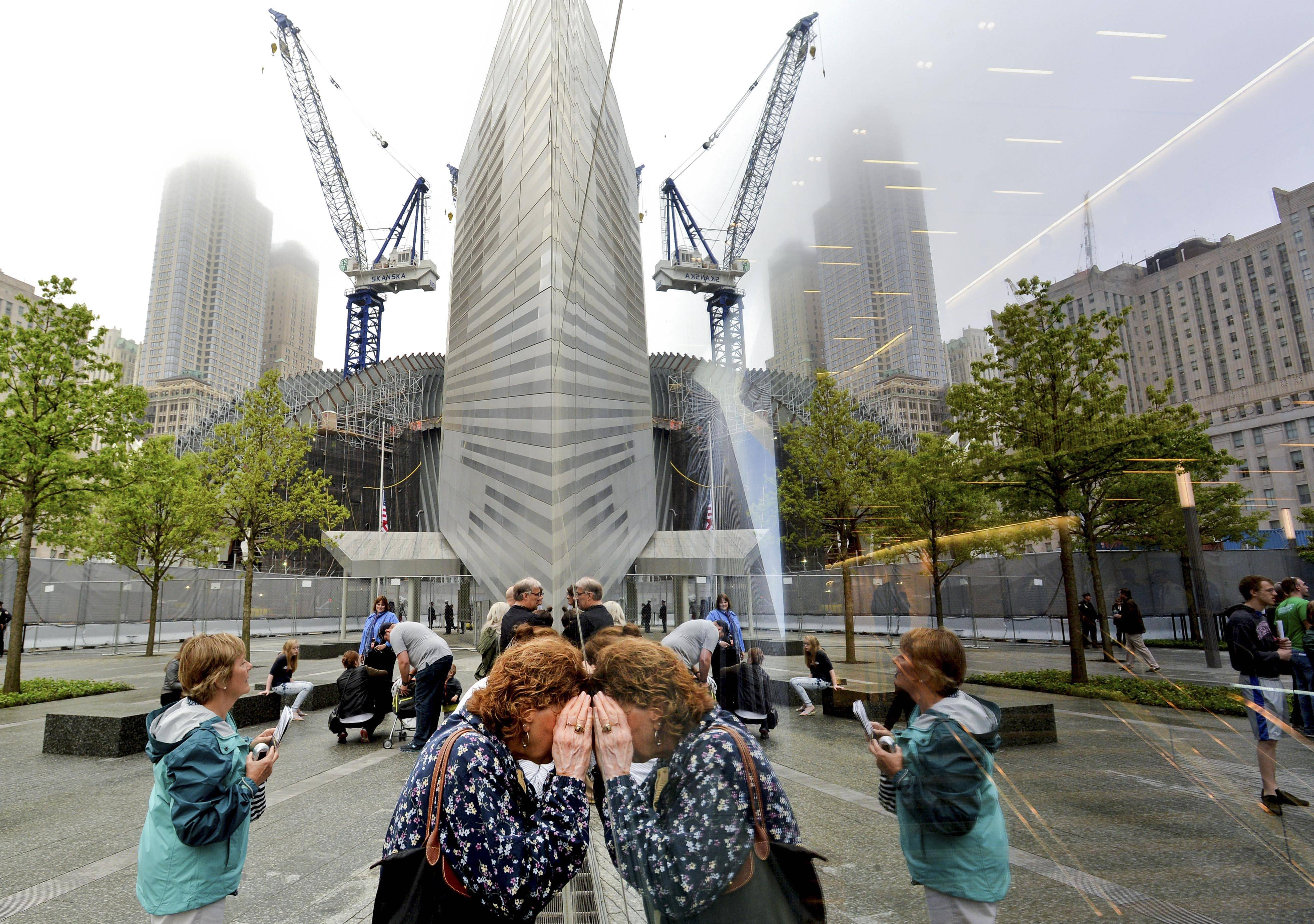 People try to look through the windows of the National September 11 Memorial Museum during the museum's dedication.