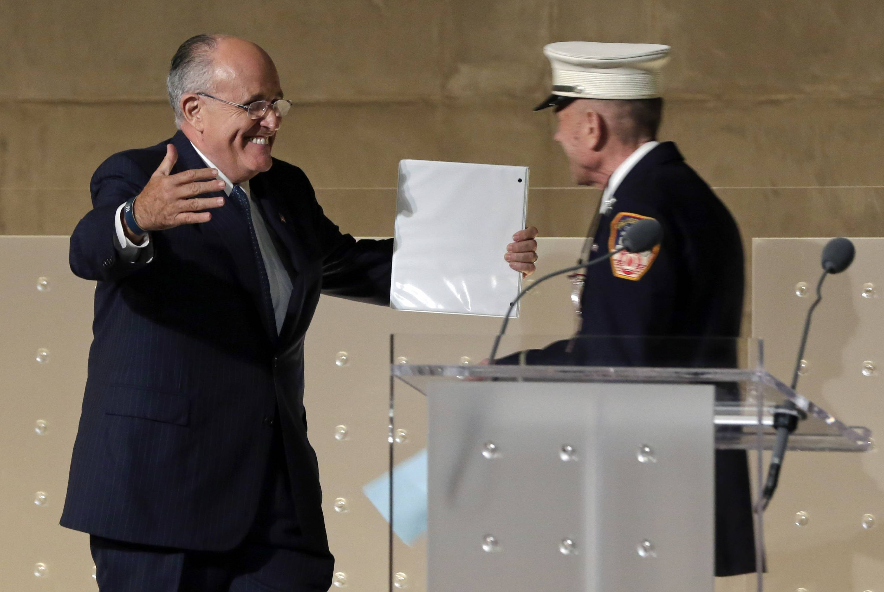 Former New York Mayor Rudolph Giuliani, left, greets New York City firefighter Mickey Kross before his speech during the dedication ceremony in Foundation Hall, of the National September 11 Memorial Museum.