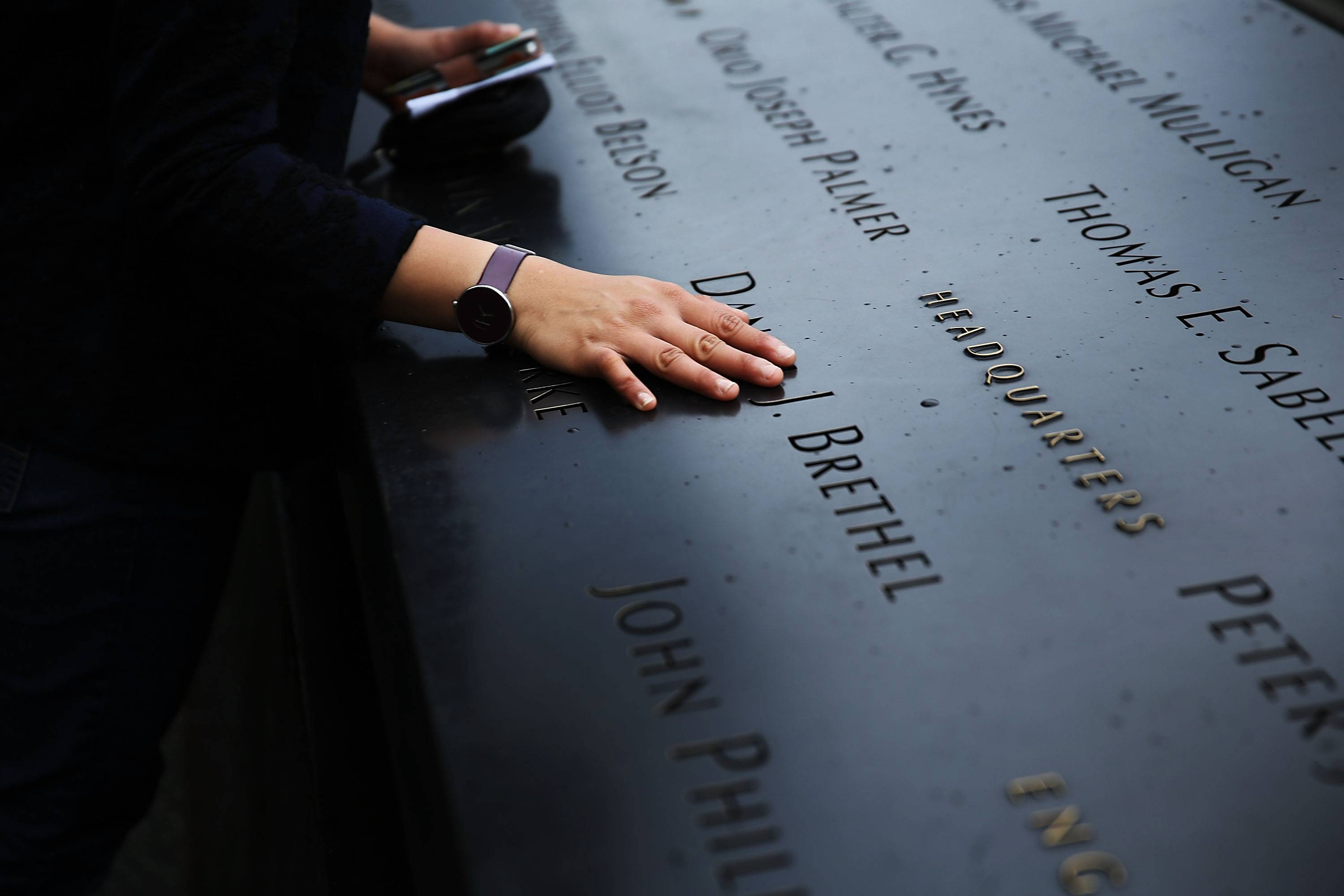 A woman places a hand on the names engraved along the South reflecting pool at the Ground Zero memorial site during the dedication ceremony.