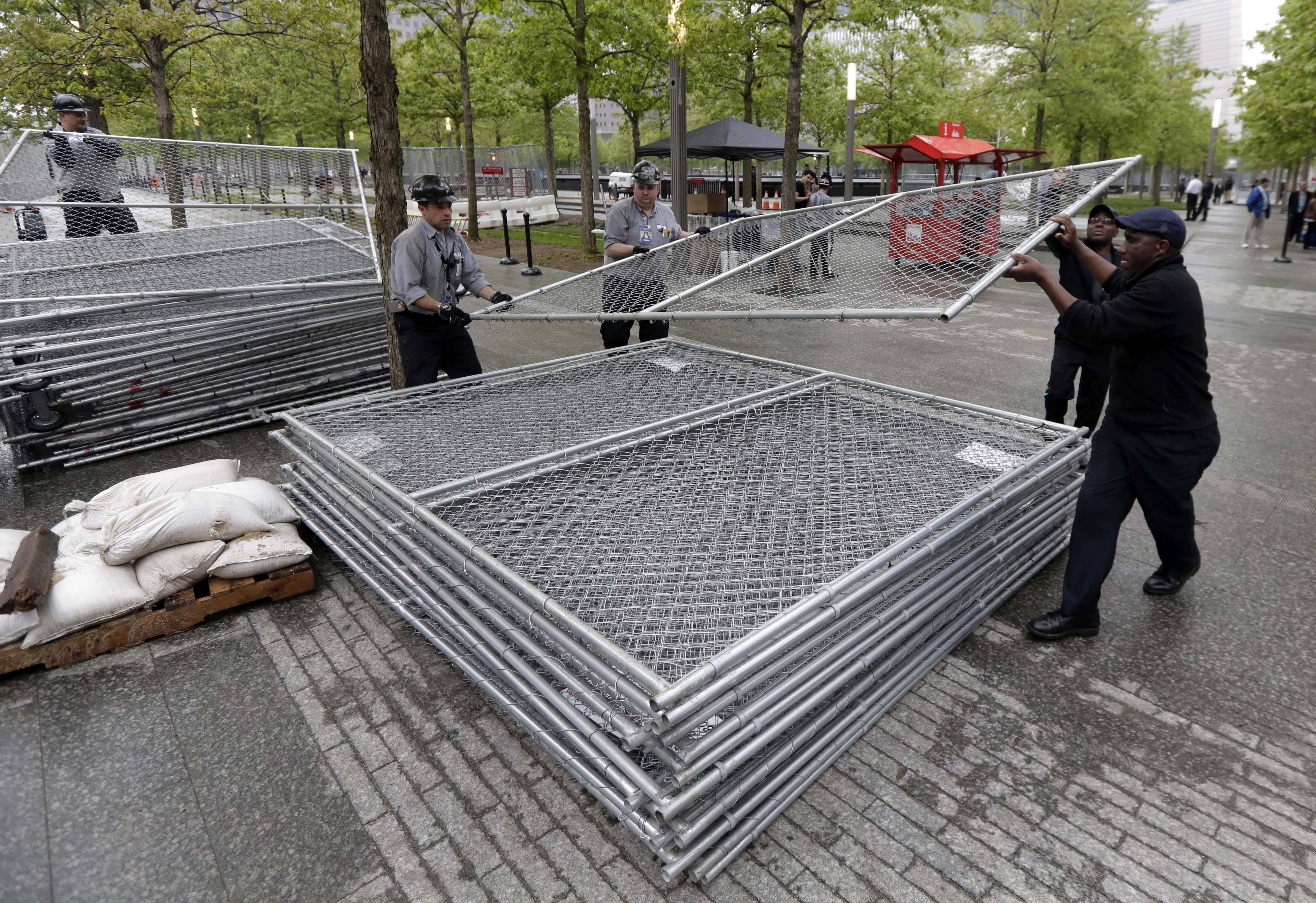 Workers on the plaza of the National September 11 Memorial & Museum stack sections of fencing removed from the venue's perimeter, in New York, Thursday, May 15, 2014.