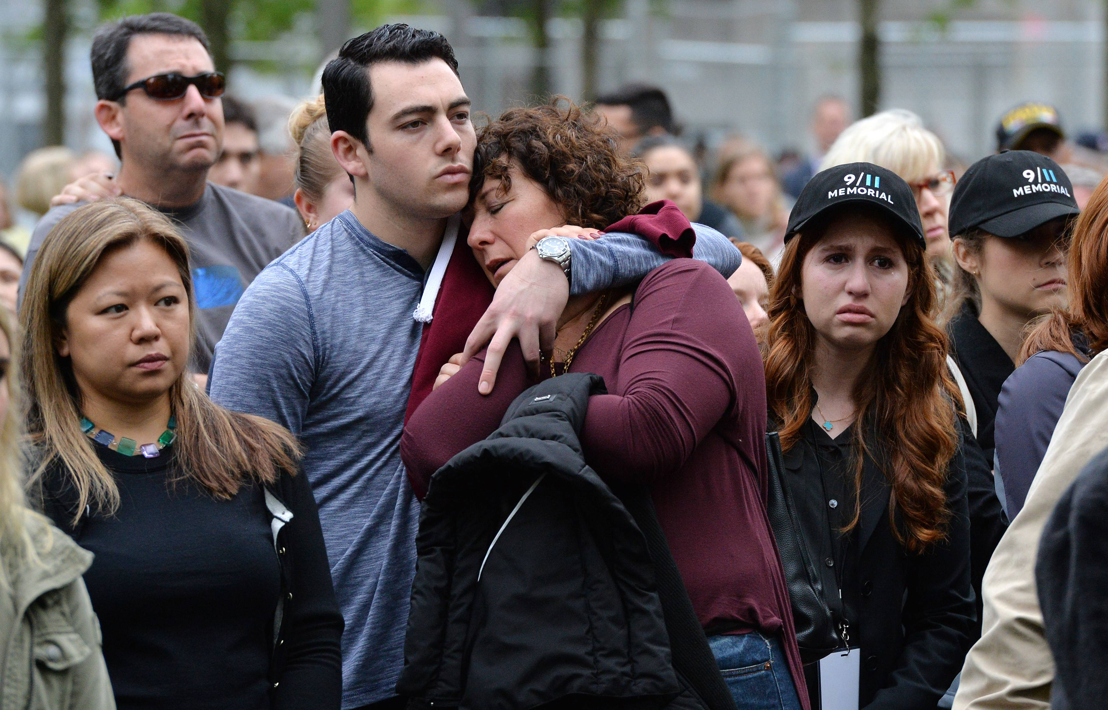 Two people embrace while gathered on the plaza of the National September 11 Memorial to watch the telecast of the dedication ceremony.