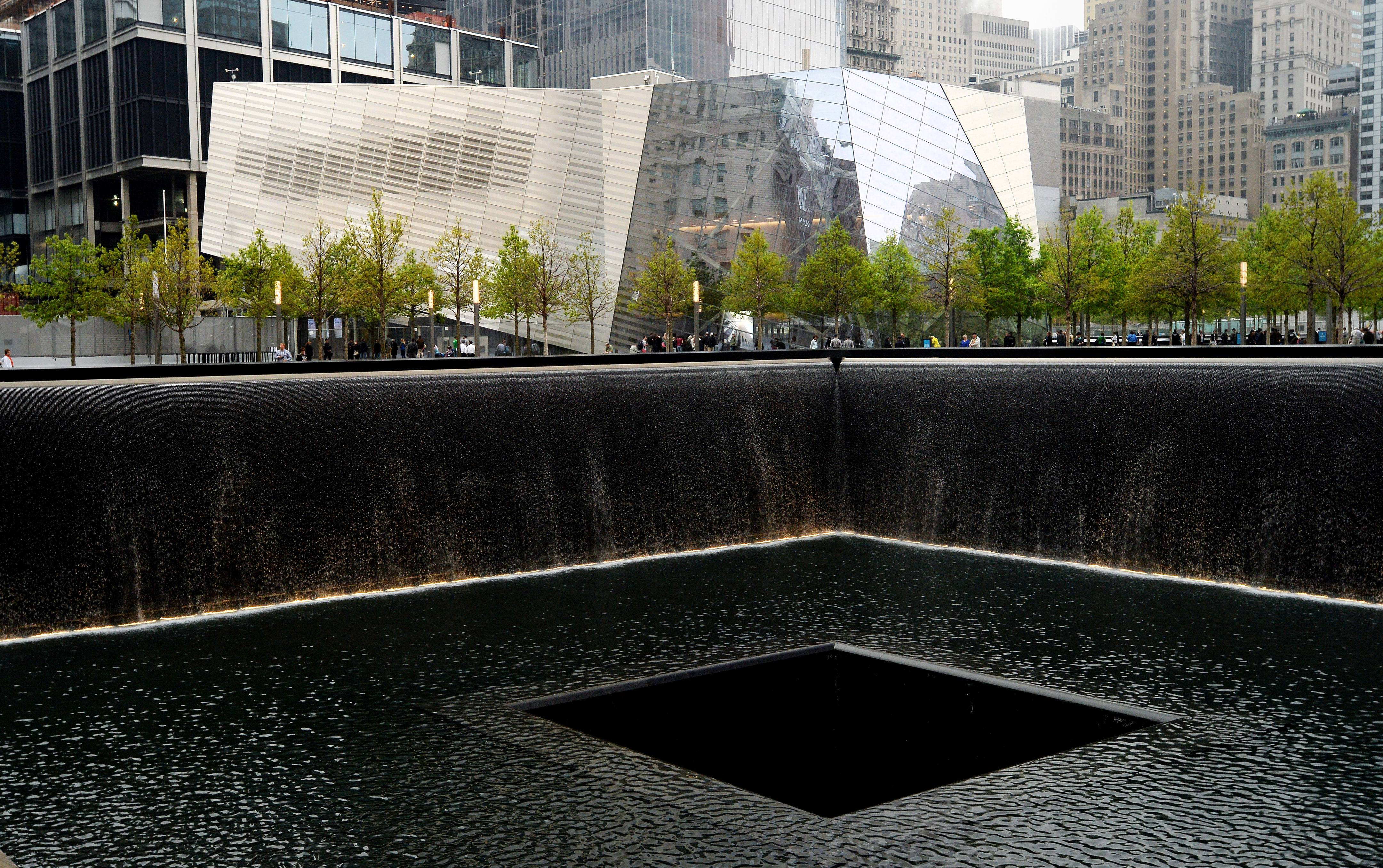 A view of the National September 11 Memorial Museum with the north reflecting pool in foreground during the museum's dedication ceremony.