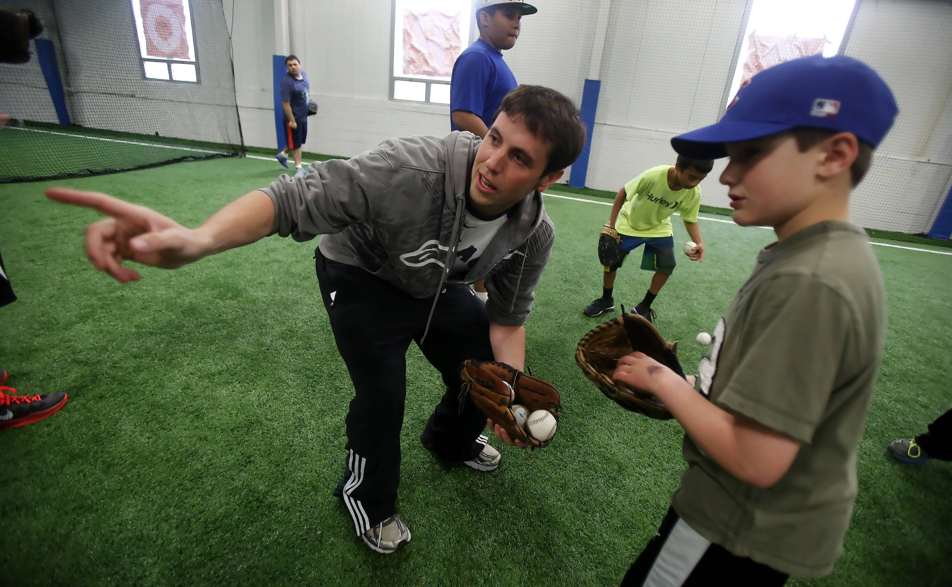 Cubs manager Justin Gebhardt directs Nicky Gebhardt, 8, during practice with the Lake Zurich Baseball and Softball Association Wednesday at the Main Street Sports Center in Lake Zurich.