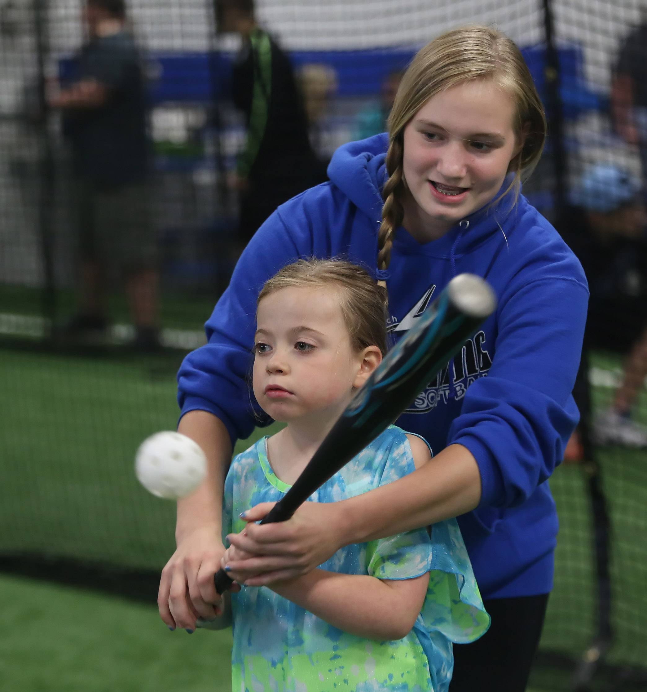 Yankees player Nicole Laubach, 7, receives help from her buddy, Riley Housinger, 12, during batting practice. In Buddy Baseball, children with special needs are paired on the field with volunteer buddies who can assist them while playing.