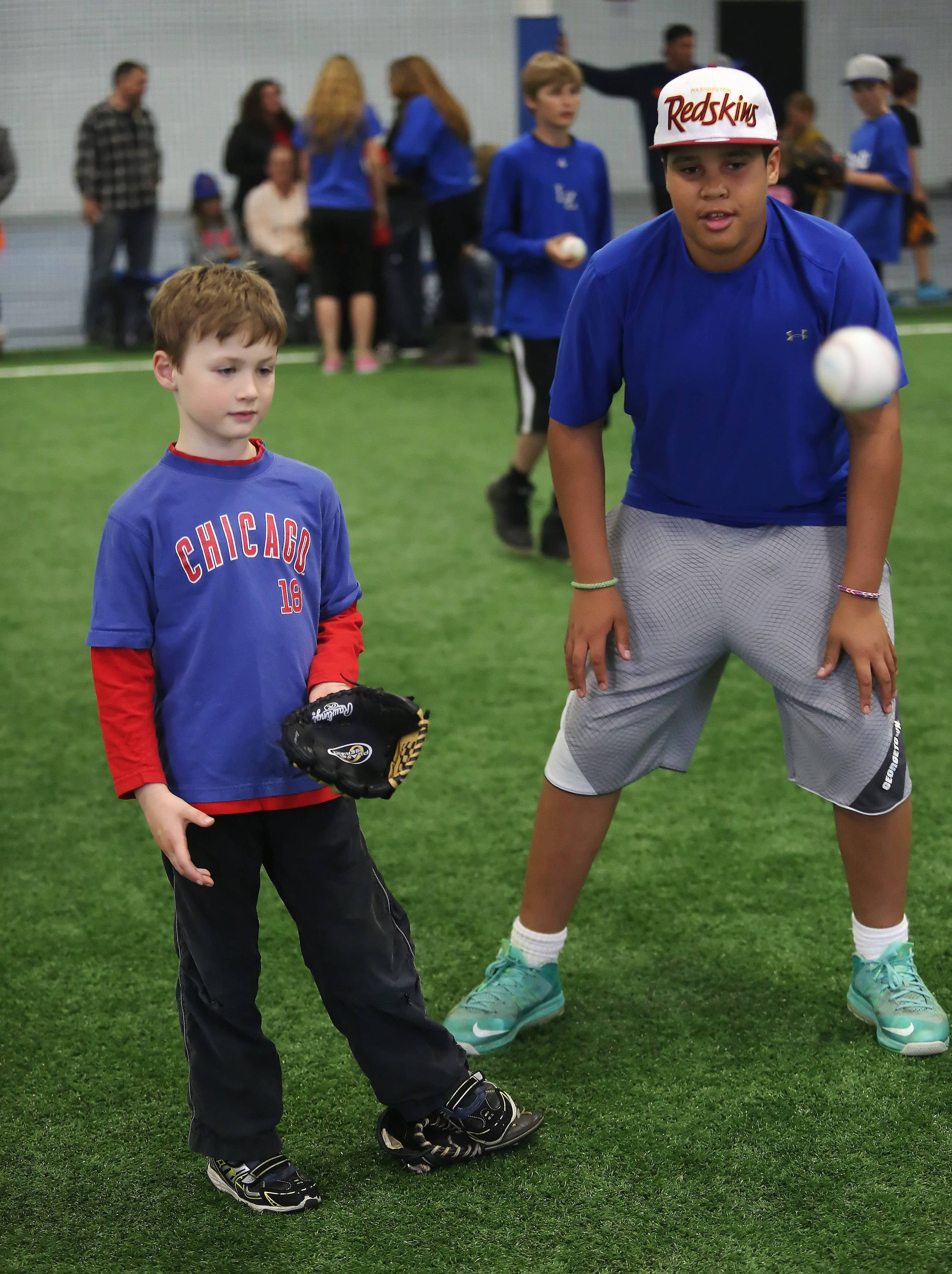 Cubs player Lucas Nelson, left, catches a ball with help from his buddy, Nathan Barnes, 13, during practice with the Lake Zurich Baseball and Softball Association Wednesday at the Main Street Sports Center in Lake Zurich.