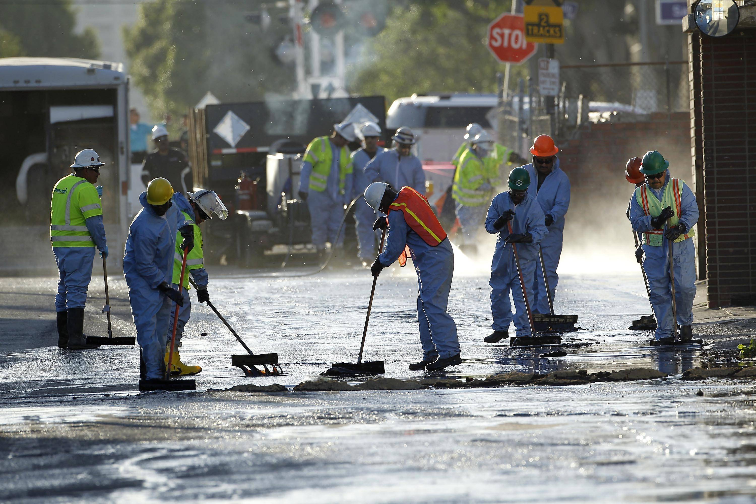 Crews sop up the remains of about 10,000 gallons of crude oil in Los Angeles on Thursday, May 15, 2014. A geyser of crude spewed 20 feet high over approximately half mile into Los Angeles streets and onto buildings early Thursday after a high-pressure pipe burst.