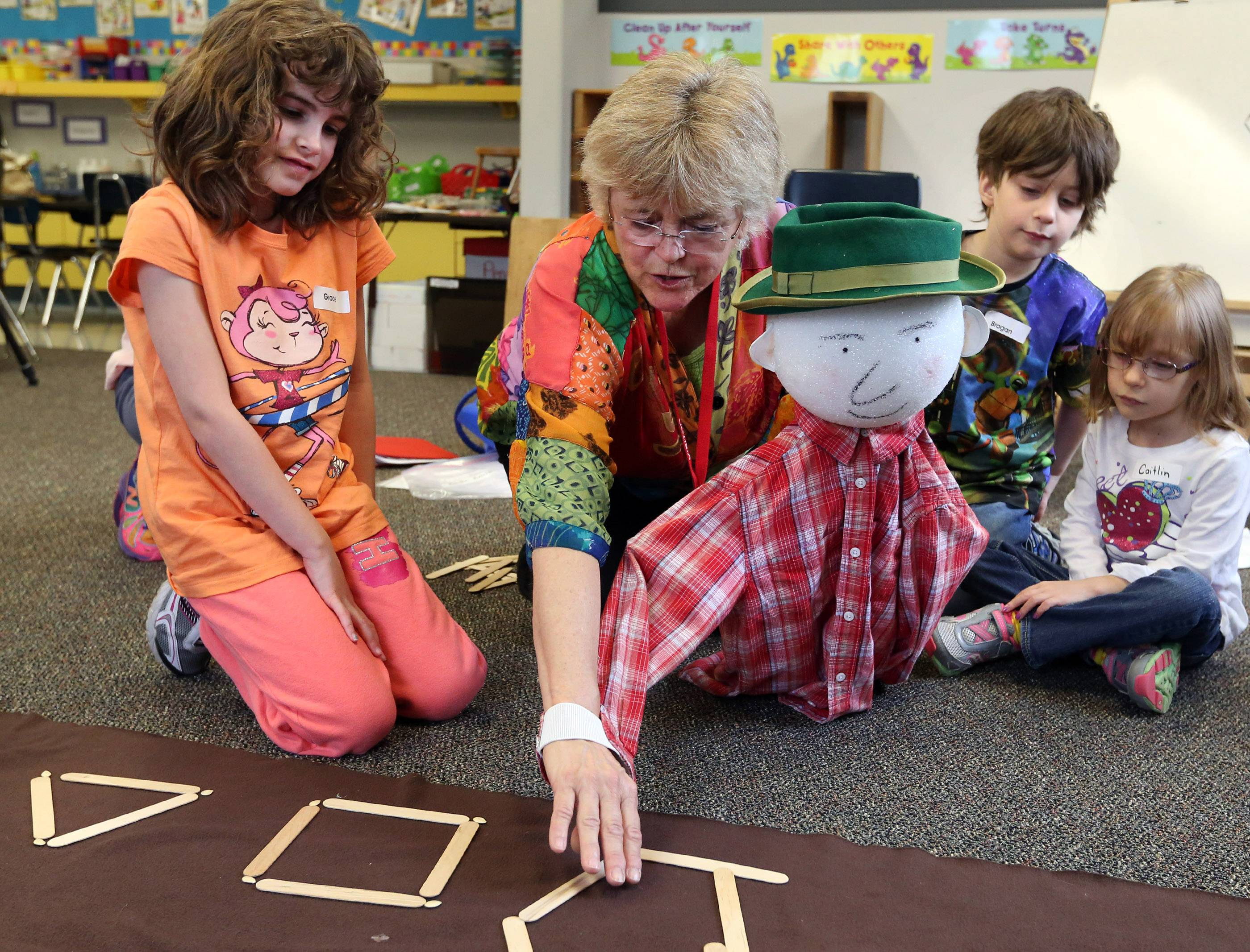 Jeanne Wall, Wolf Trap master teaching artist, uses a puppet to help kindergartner Grace Avlia, left, create patterns with sticks Wednesday during a unique early childhood STEM program in Sue Matkovic's class at Kimball Hill School in Rolling Meadows.