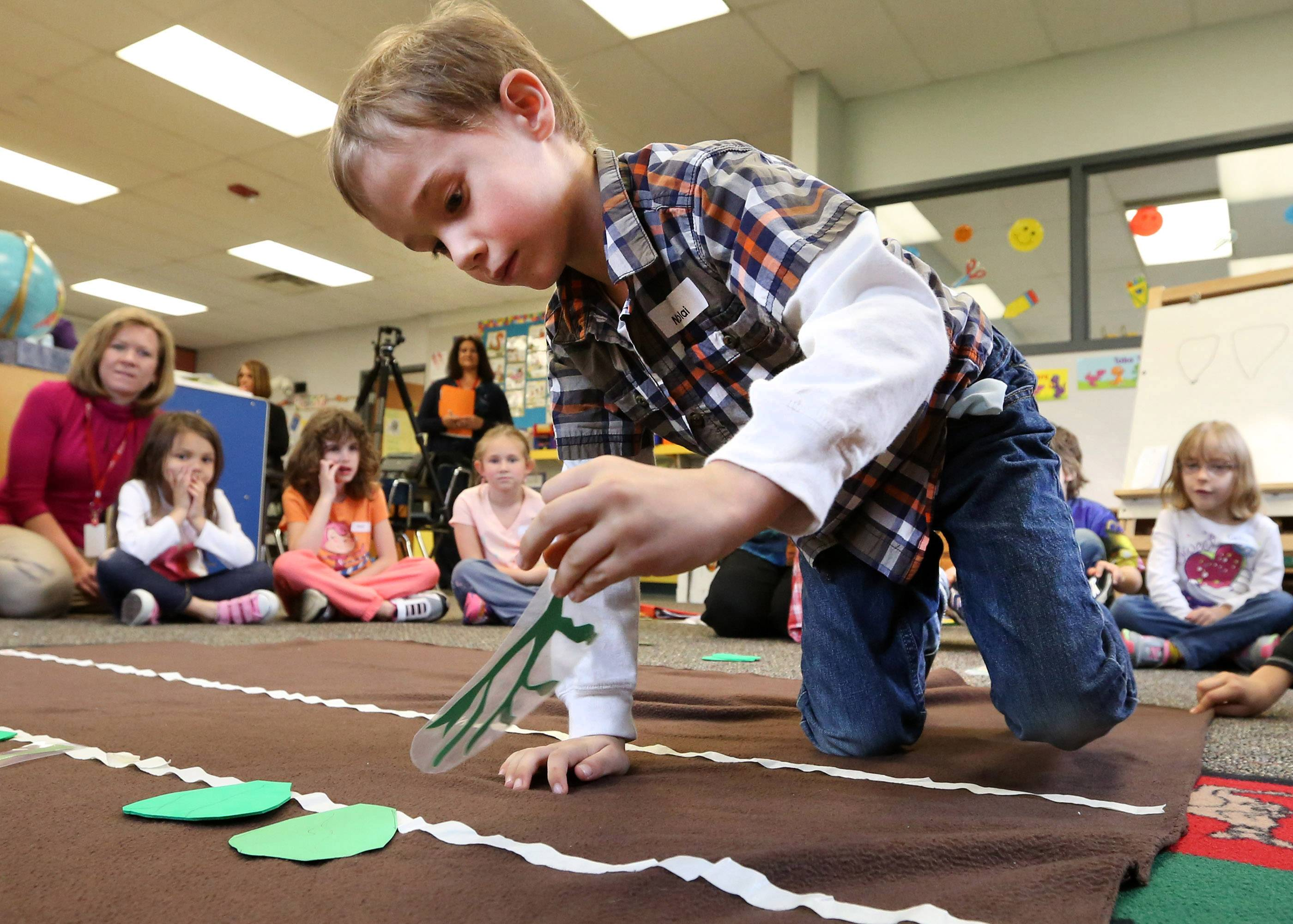 Kindergartner Nikolai Polus places a paper on a dirt-colored cloth during a program taught by Jeanne Wall, Wolf Trap master teaching artist, at Kimball Hill School in Rolling Meadows.