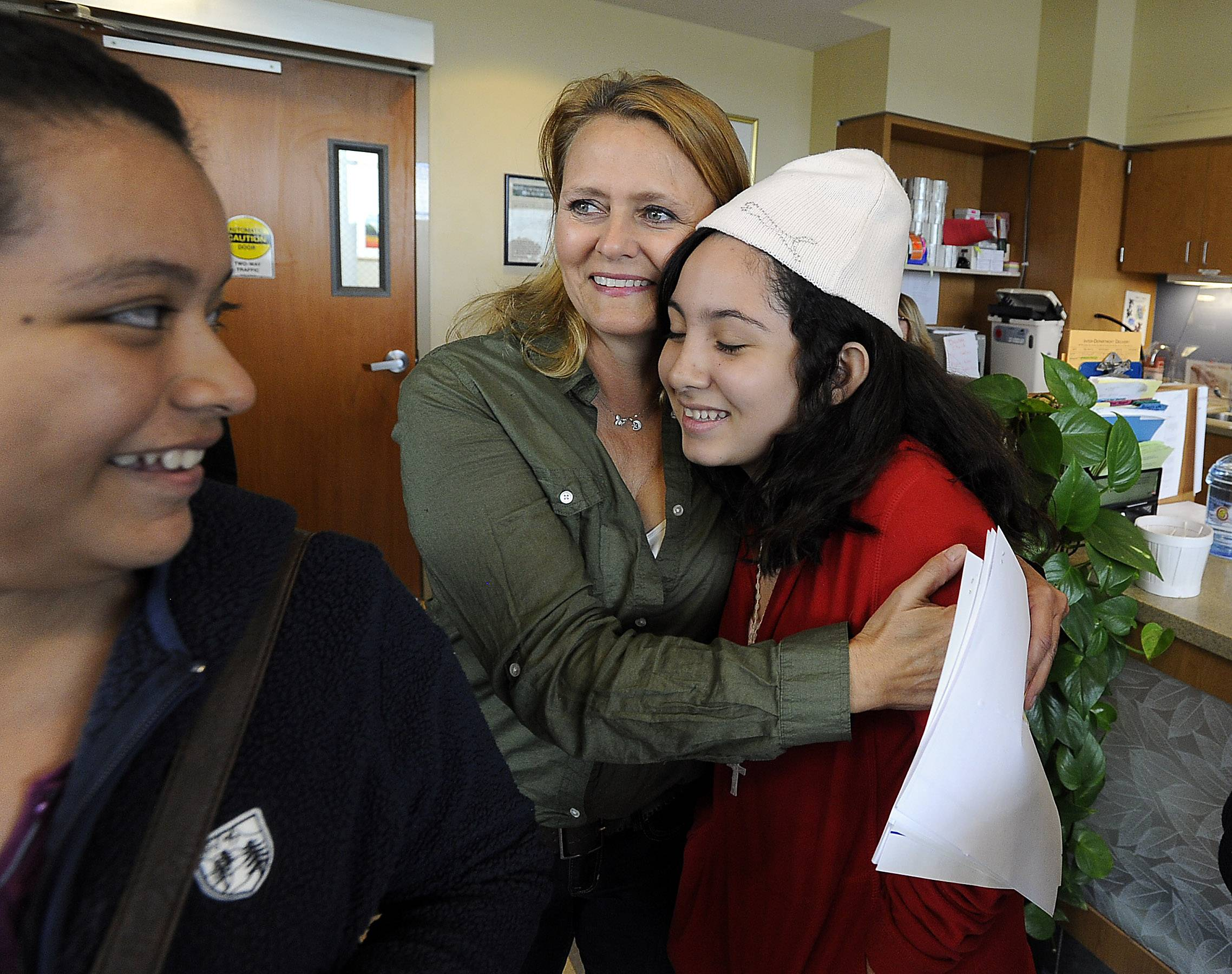 Host mom Marianna Bagshaw of Hawthorn Woods hugs Andrea Escalante, 12, as Leslie Salas, 13, looks on Wednesday at Advocate Good Shepherd Hospital in Lake Barrington. The Salvadoran girls were there getting tested for their upcoming tachycardia surgery which will cure them of their irregular heartbeats.