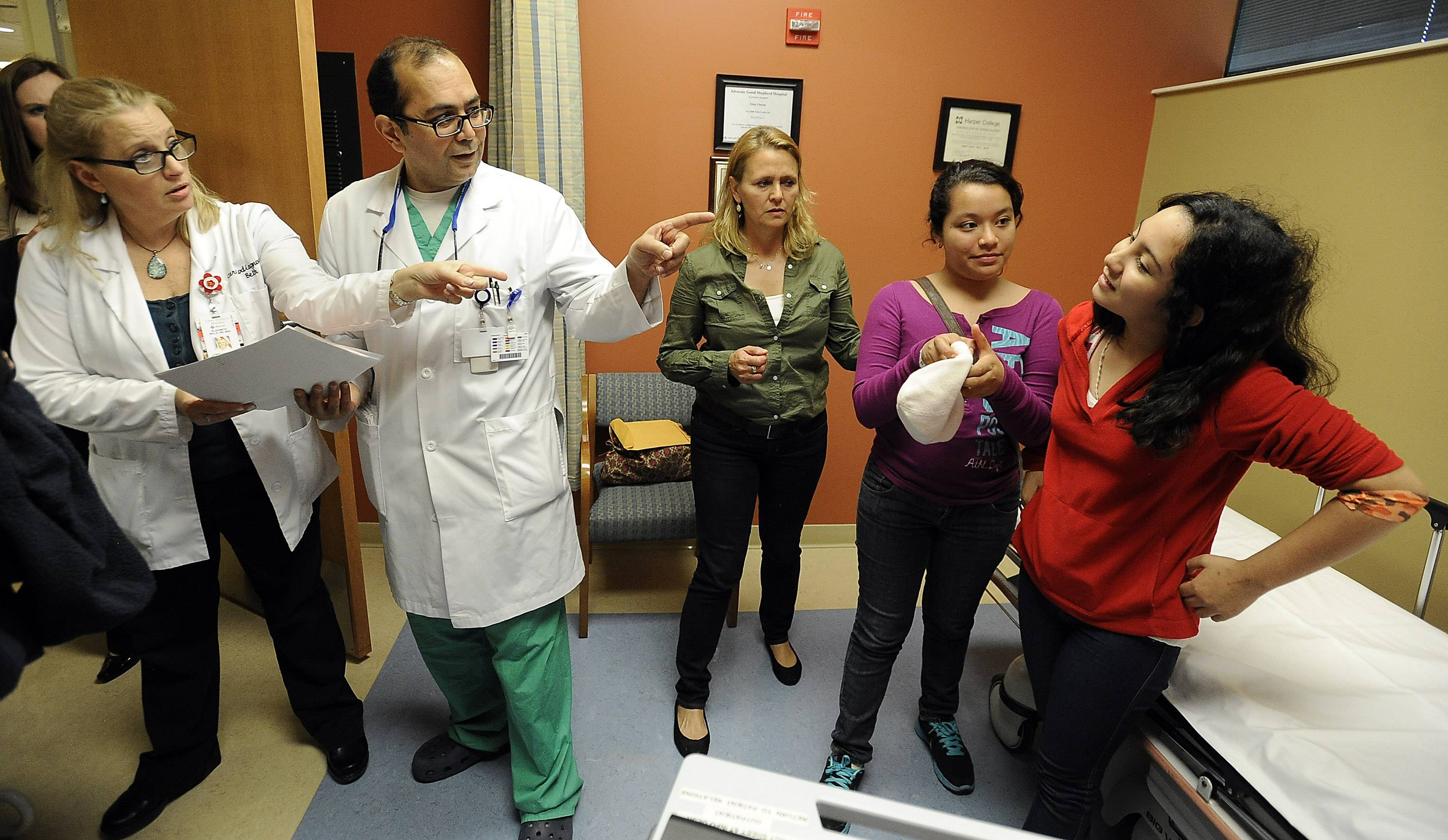 Host mom Marianna Bagshaw of Hawthorn Woods, center, looks on as Leslie Salas, 13, and Andrea Escalante, 12, and Dr. Mehran Jabbarzadeh discuss their upcoming surgery to fix their irregular heartbeats.