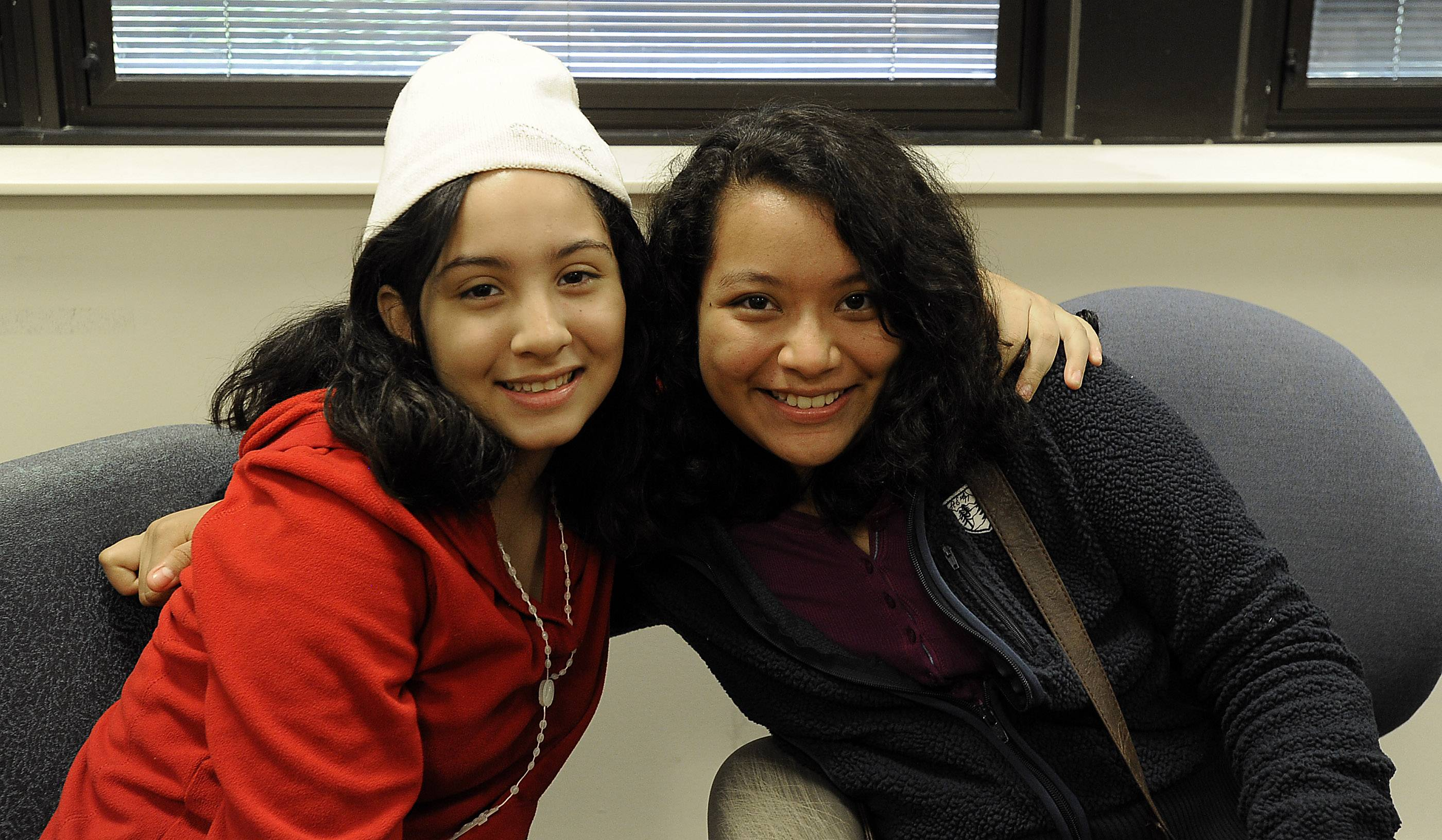 Andrea Escalante, 12, left, and Leslie Salas, 13, both of El Salvador, have only known each other two days but already have become fast friends. The two flew from El Salvador to Chicago on Tuesday, their first trip on a plane and first time away from their home country.