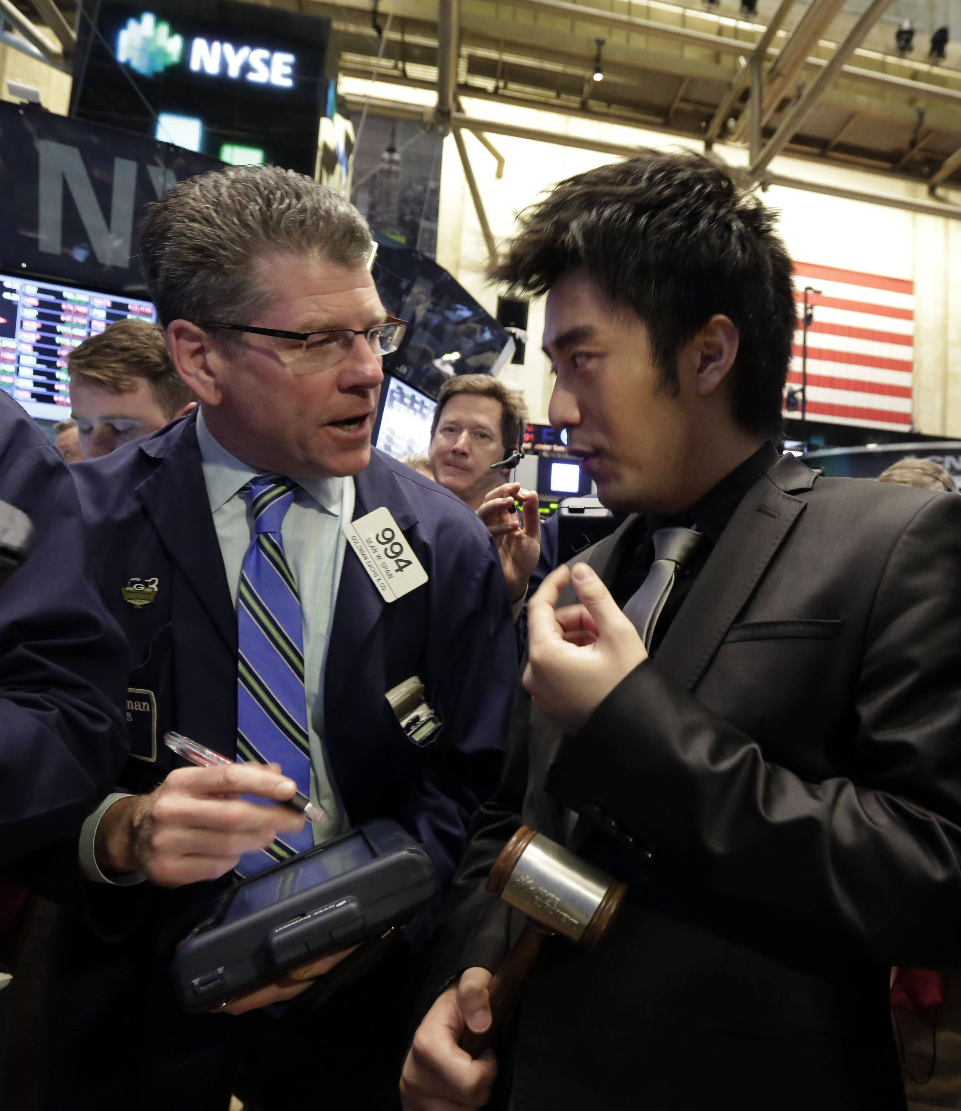 CEO Leo Ou Chen of Jumei.com, right, talks Friday with trader Sean Spain on the floor of the New York Stock Exchange before his company's IPO begins trading.