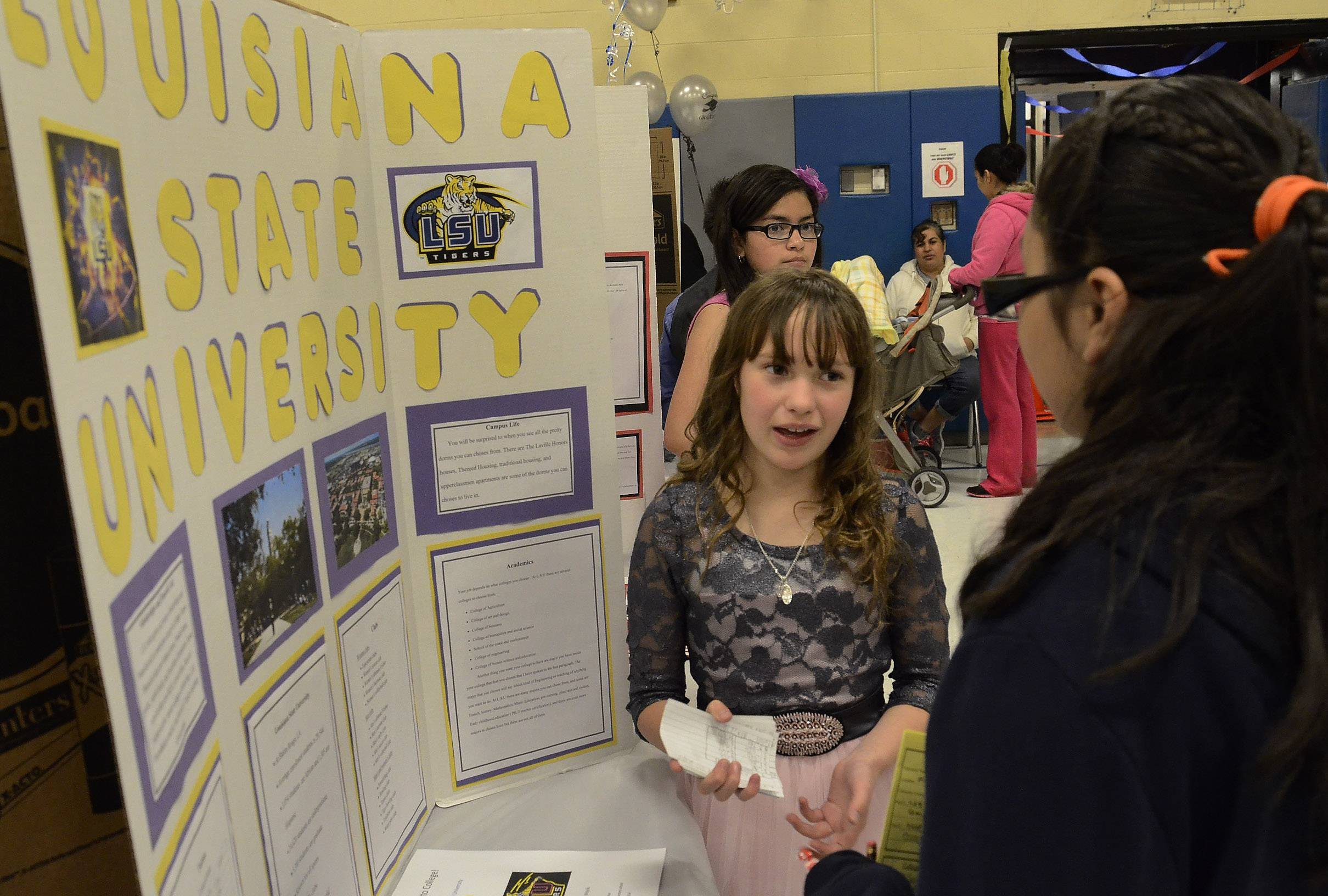 Victoria Wojcik, left, pitches Louisiana State University to Ashley Huerta on Friday as Ontarioville Elementary School fifth-graders host a college fair,