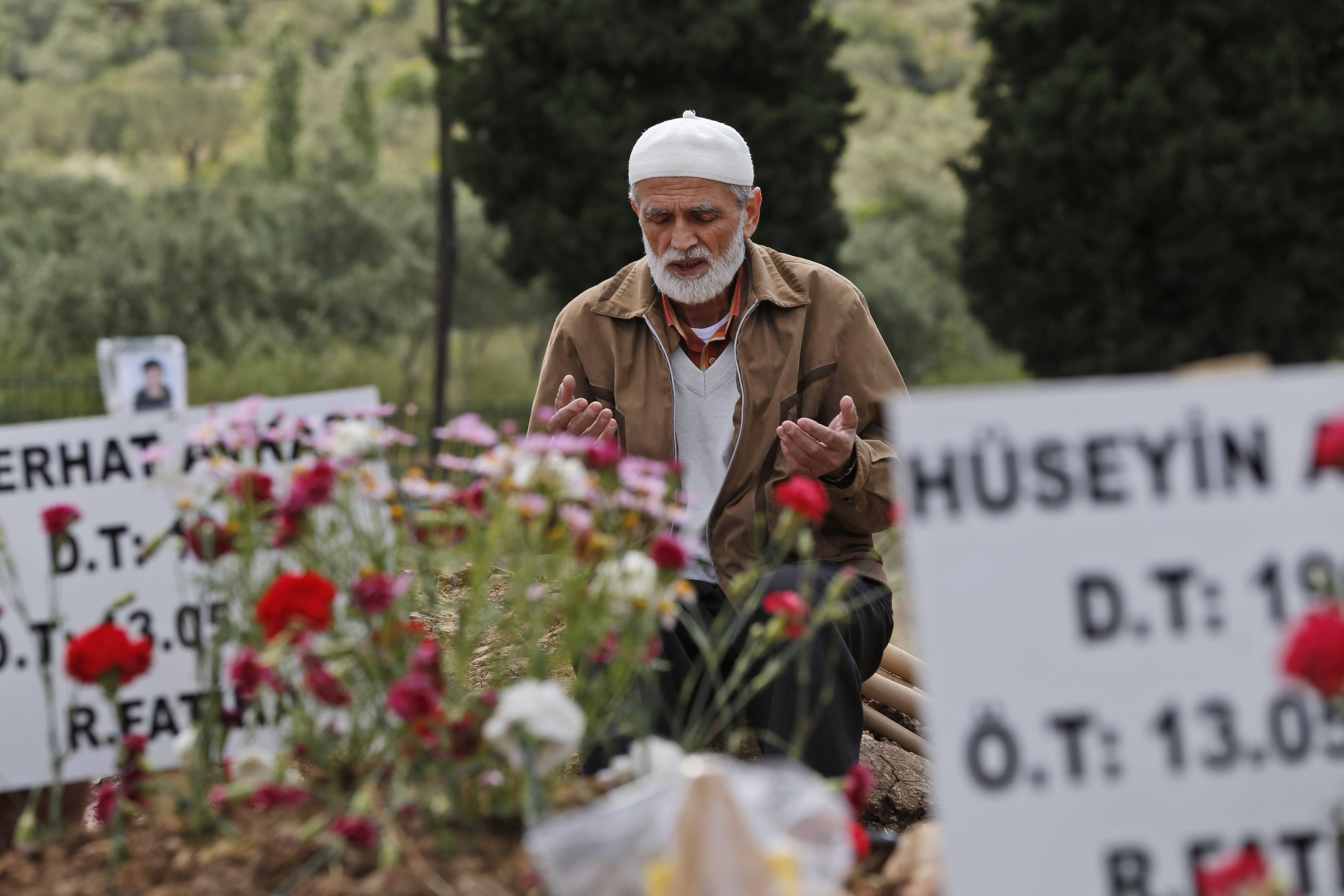 A man offers his prayers next to the graves of victims of the mine accident in Soma, Turkey, Friday, May 16, 2014. A Turkish mining company defended its safety record Friday, four days after more than 280 people died in an underground blaze at its coal mine in western Turkey.