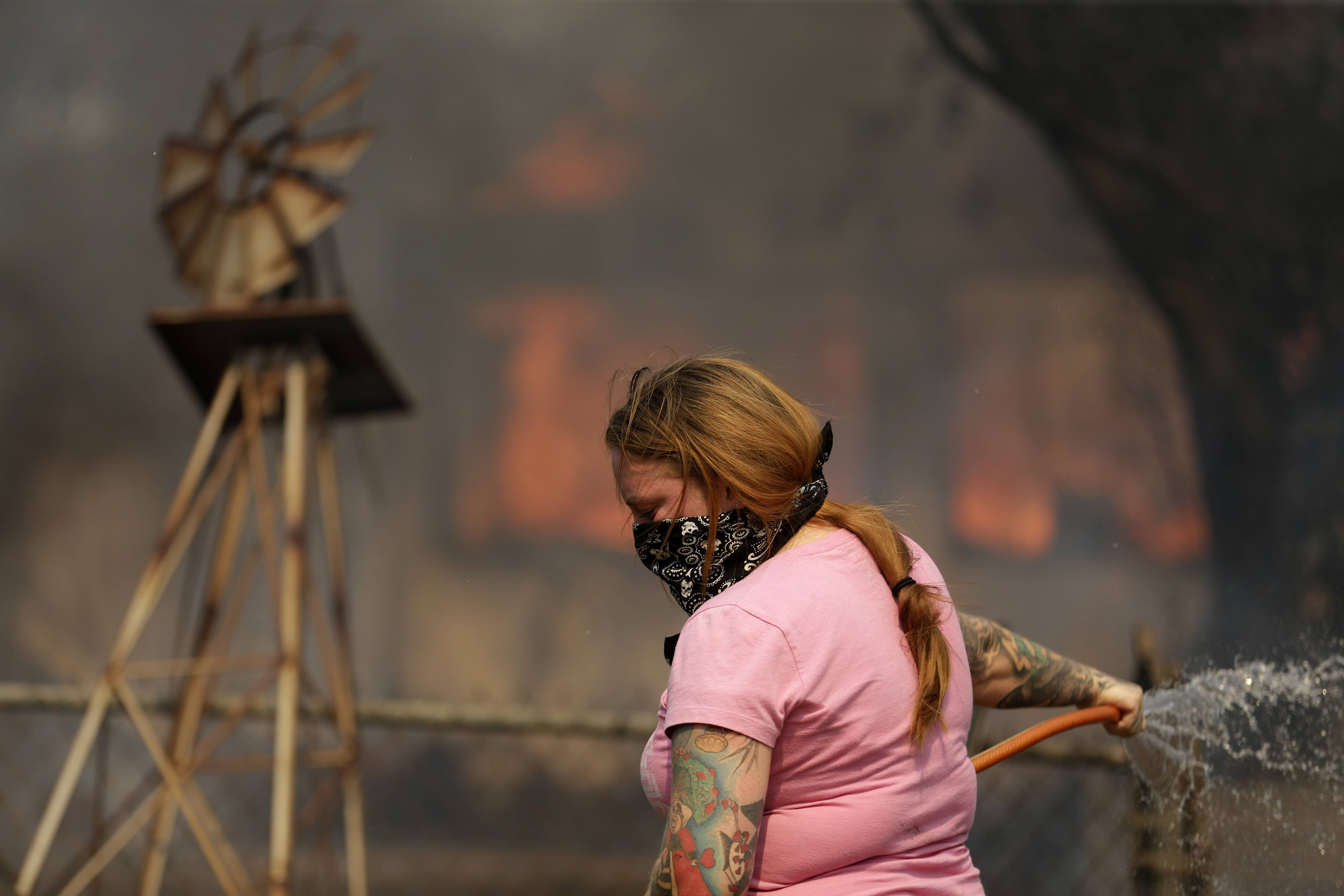 A woman douses water from a hose around her home as her neighbor's home burns during a wildfire Thursday, May 15, 2014, in Escondido, Calif.