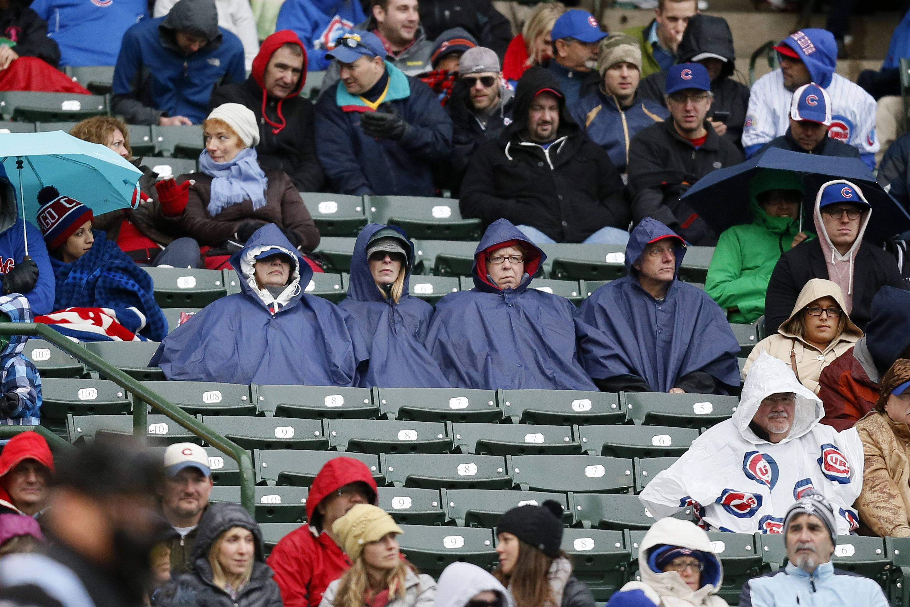 Fans watch the game between the Brewers and Cubs as a cold rain falls Friday at Wrigley Field.