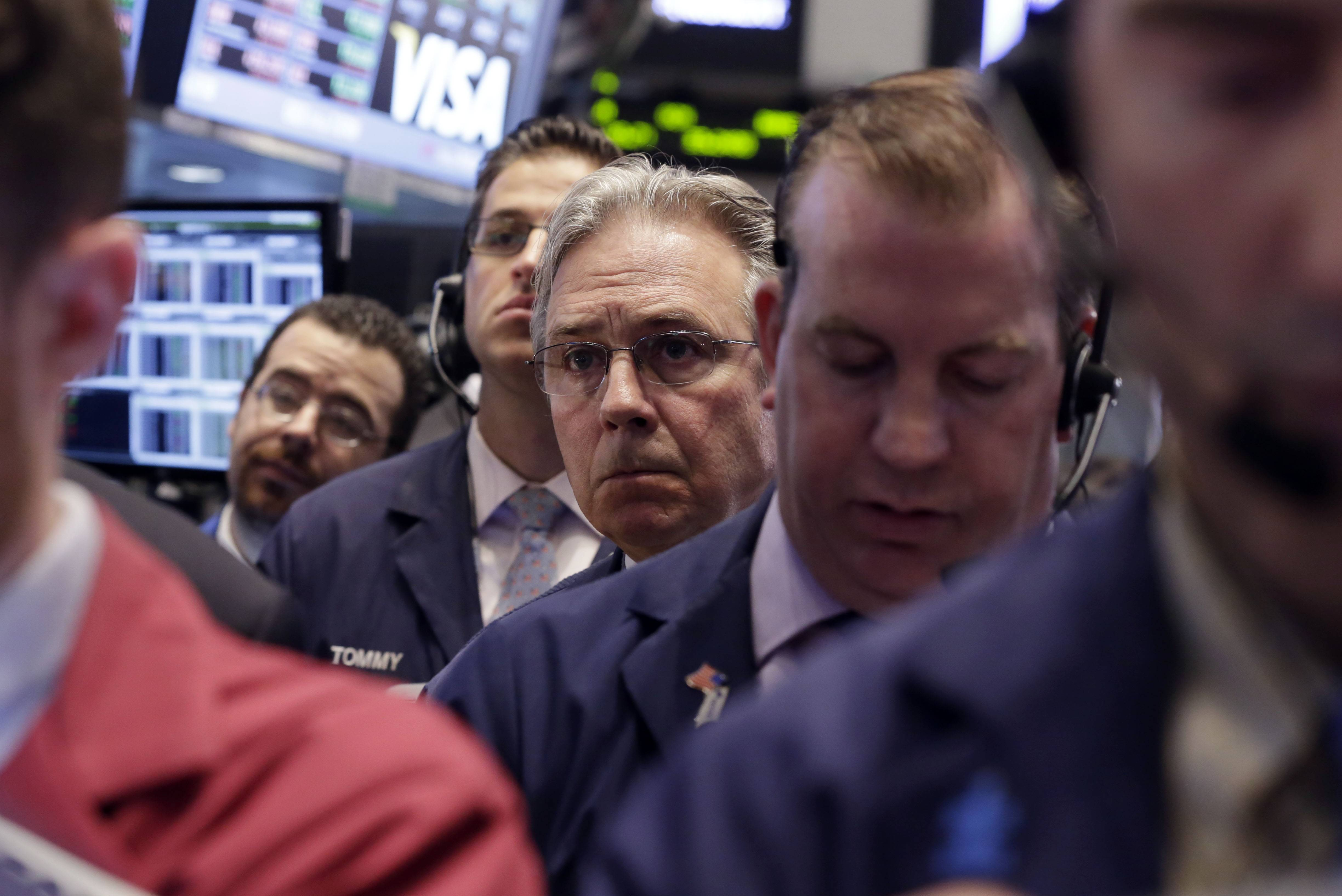 Thomas Kaye, third from right, works with fellow traders Friday on the floor of the New York Stock Exchange. Just a few months ago, investors thought the economy would expand rapidly this year. Now they're not so sure.