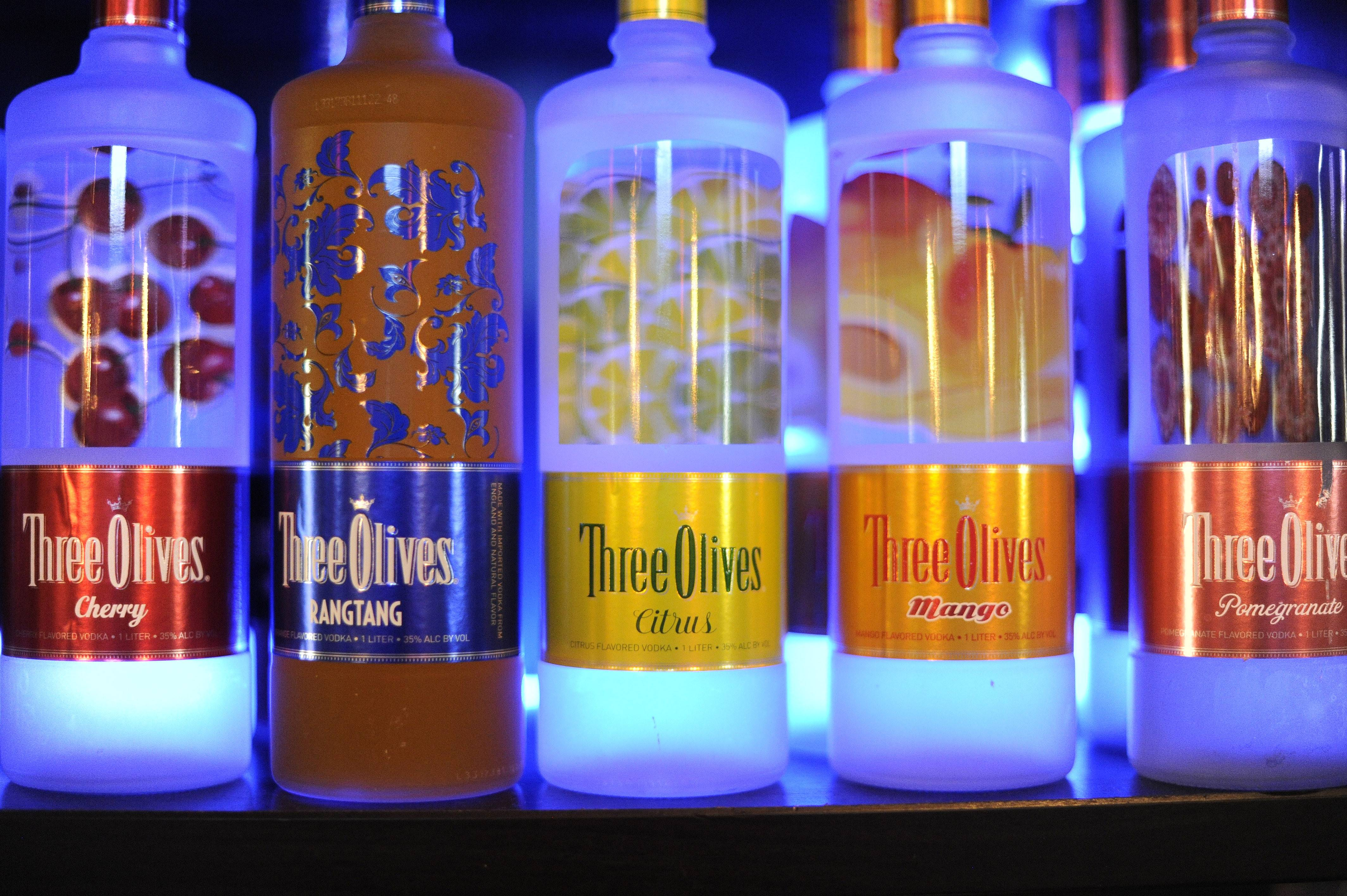 Blue back lights illuminate liquor bottles at The Range Grill & Tap.