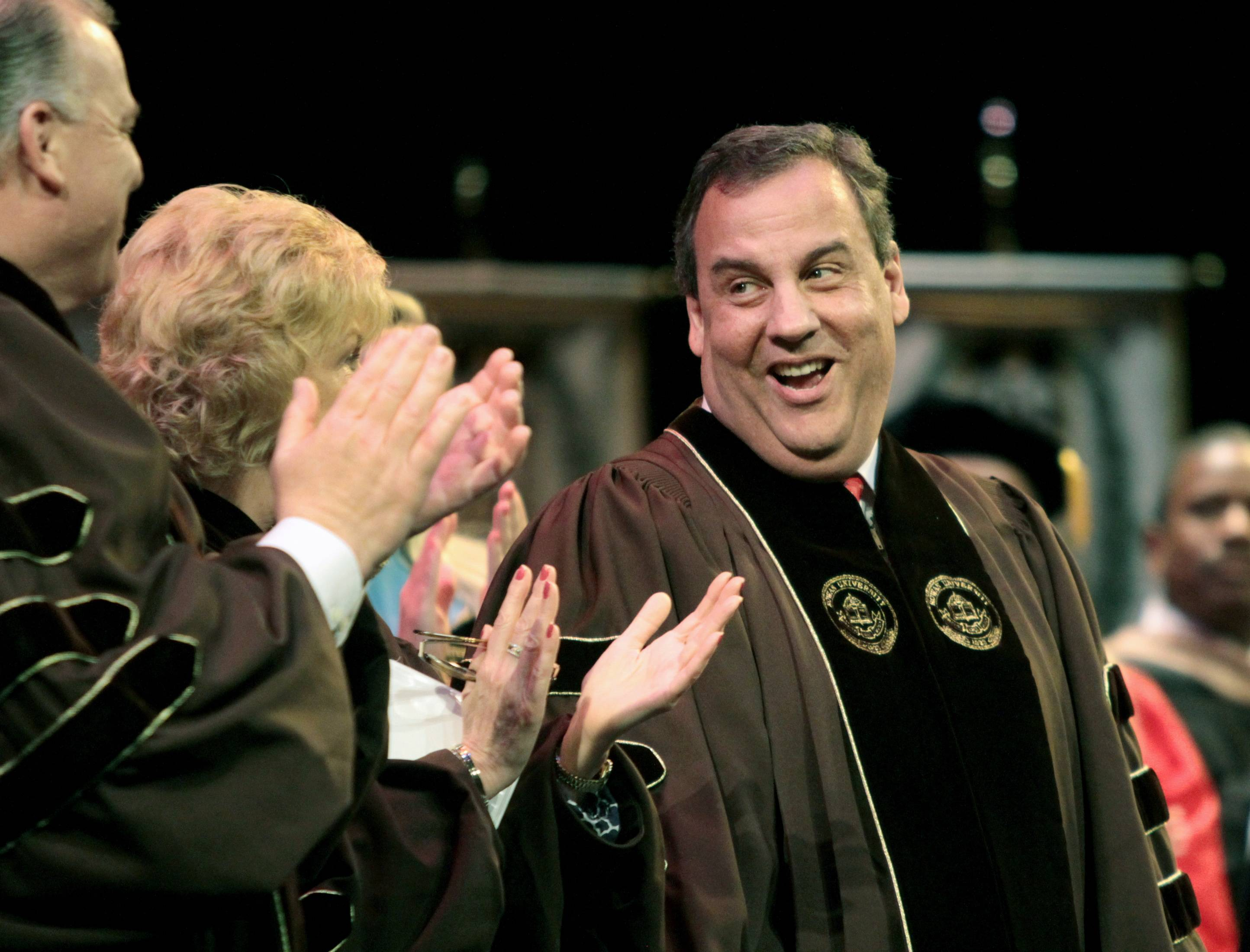 Gov. Chris Christie smiles Friday at state Senate President Stephen Sweeney after delivering his address during Rowan University's Commencement in Glassboro, N.J.  Christie told the graduates that their new degrees will provide opportunities but do not guarantee success.
