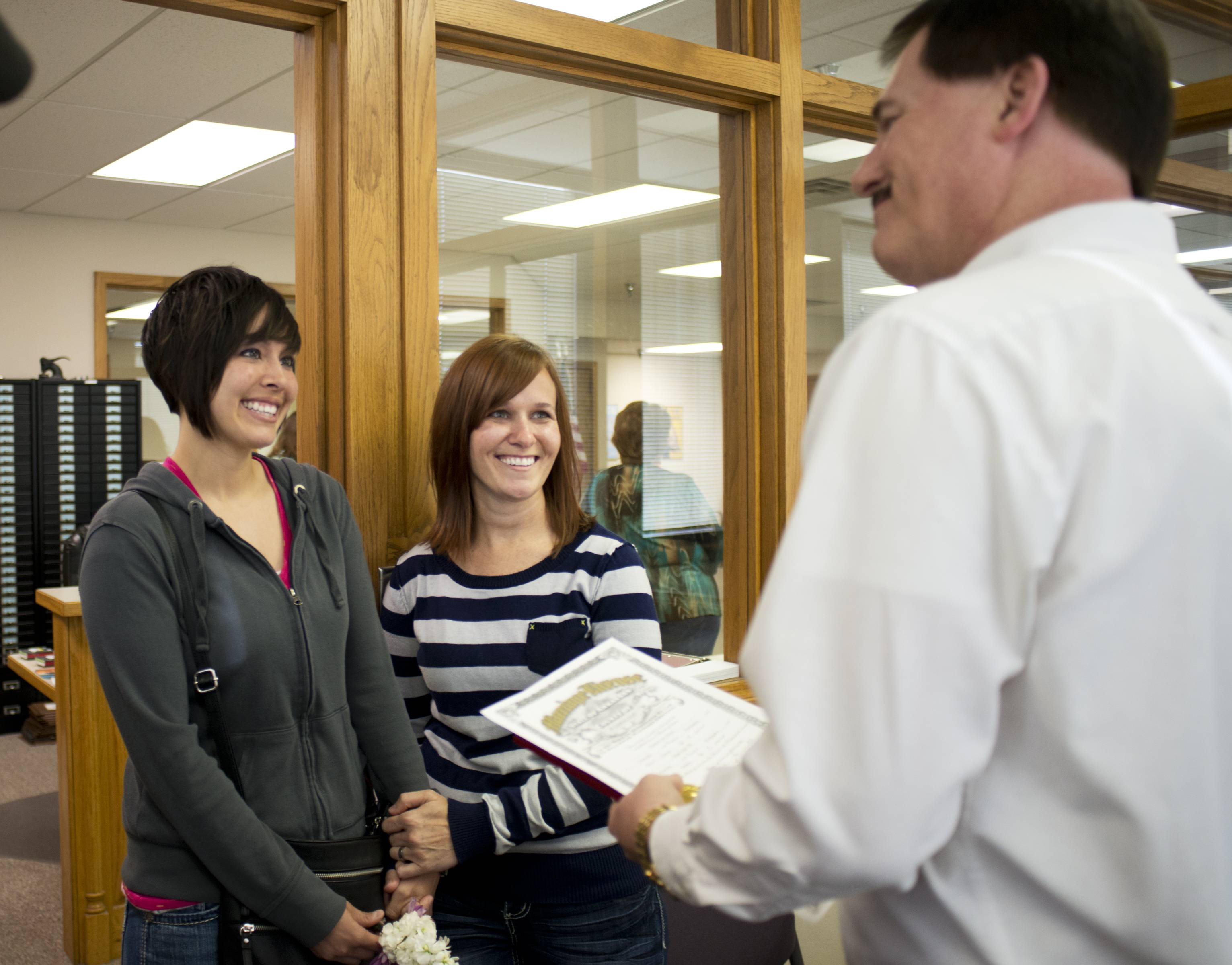 Beth Moore, left, and Abby Hill exchange vows in a marriage ceremony performed Friday by Jeremy Hernandez at the Washington County courthouse in Fayetteville, Arkansas. Later Friday, the state's Supreme Court halted the distribution of marriage licenses to same-sex couples.