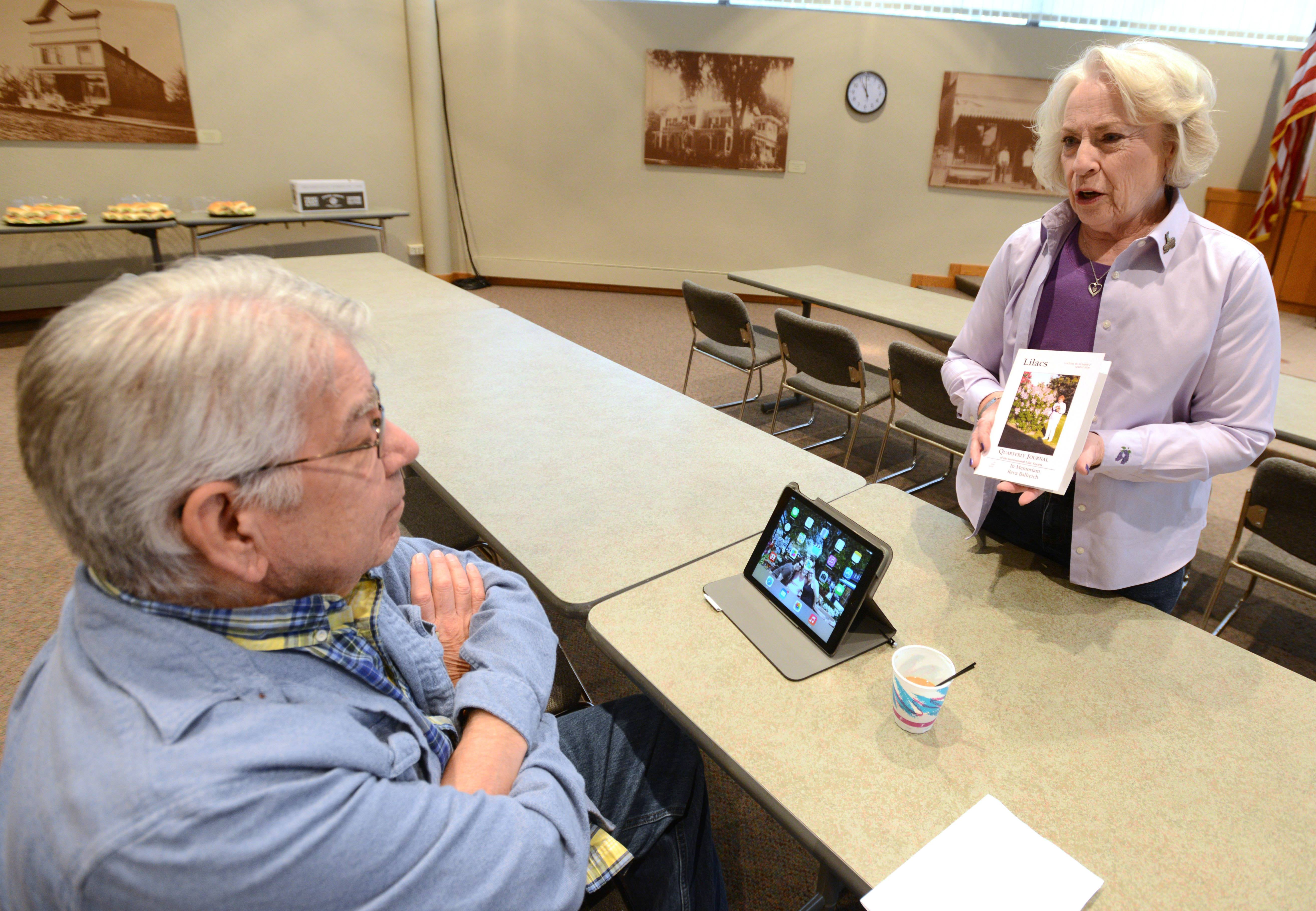 "Fred Llaguno of Lombard gets some tips from local lilac expert Marymae Meyer at ""Lilacs 101,"" which was held Friday at village hall. Meyer answered common questions about lilacs, such as bloom time and the size and shape of individual lilac plants."