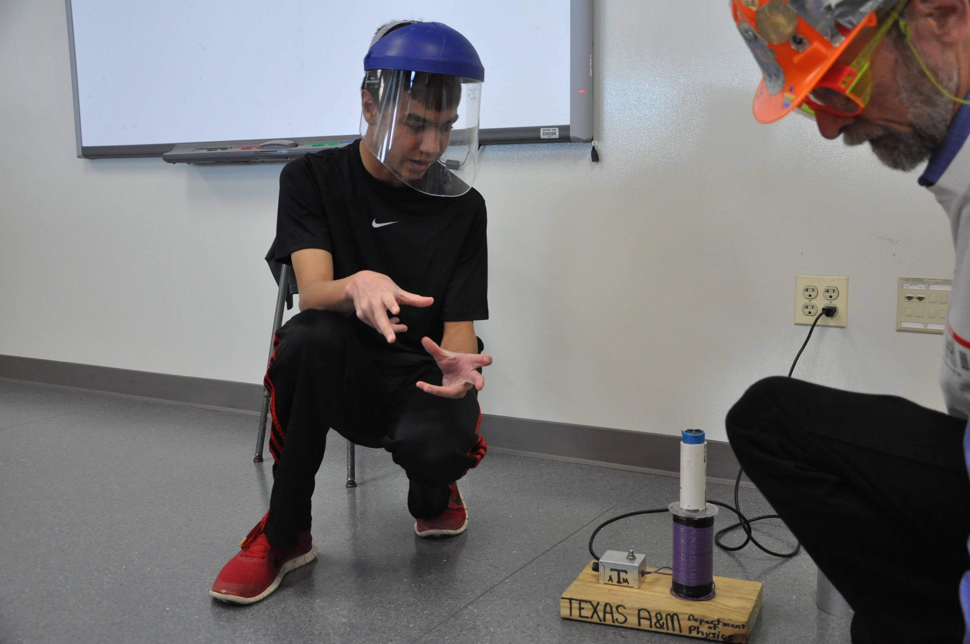 "Jefferson Junior High eighth-grader Jay Bhatia and retired Naperville North chemistry teacher Lee Marek prepare a ""Jumping Ring"" science demonstration using a contraption Marek got by trading with scientists from Texas A&M University."