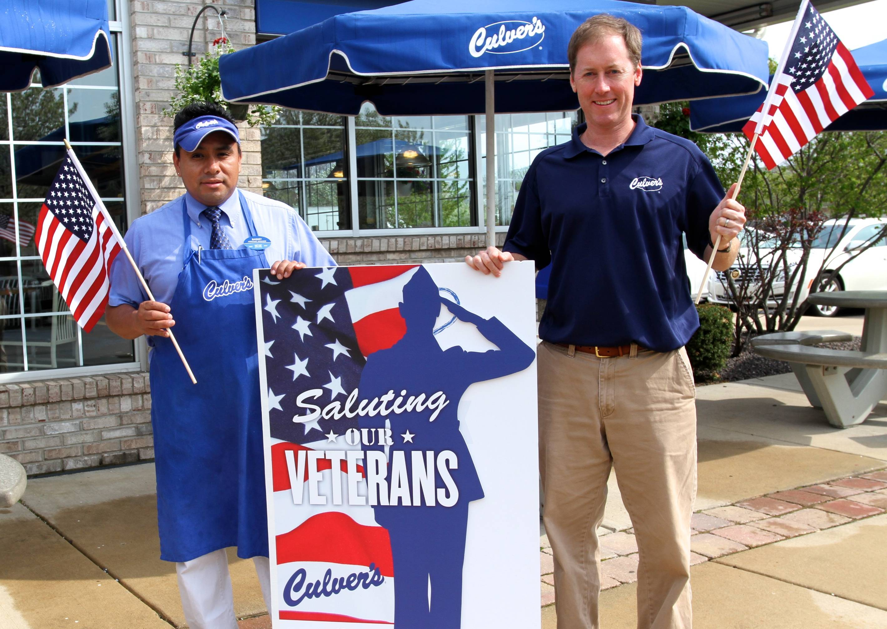 Culver's of Buffalo Grove owner Kevin Weasler, right, and restaurant manager Barney Mendoza display the giant thank-you card it will ask guests to sign as part of the May 20 Day of Giving to benefit Honor Flight Chicago.
