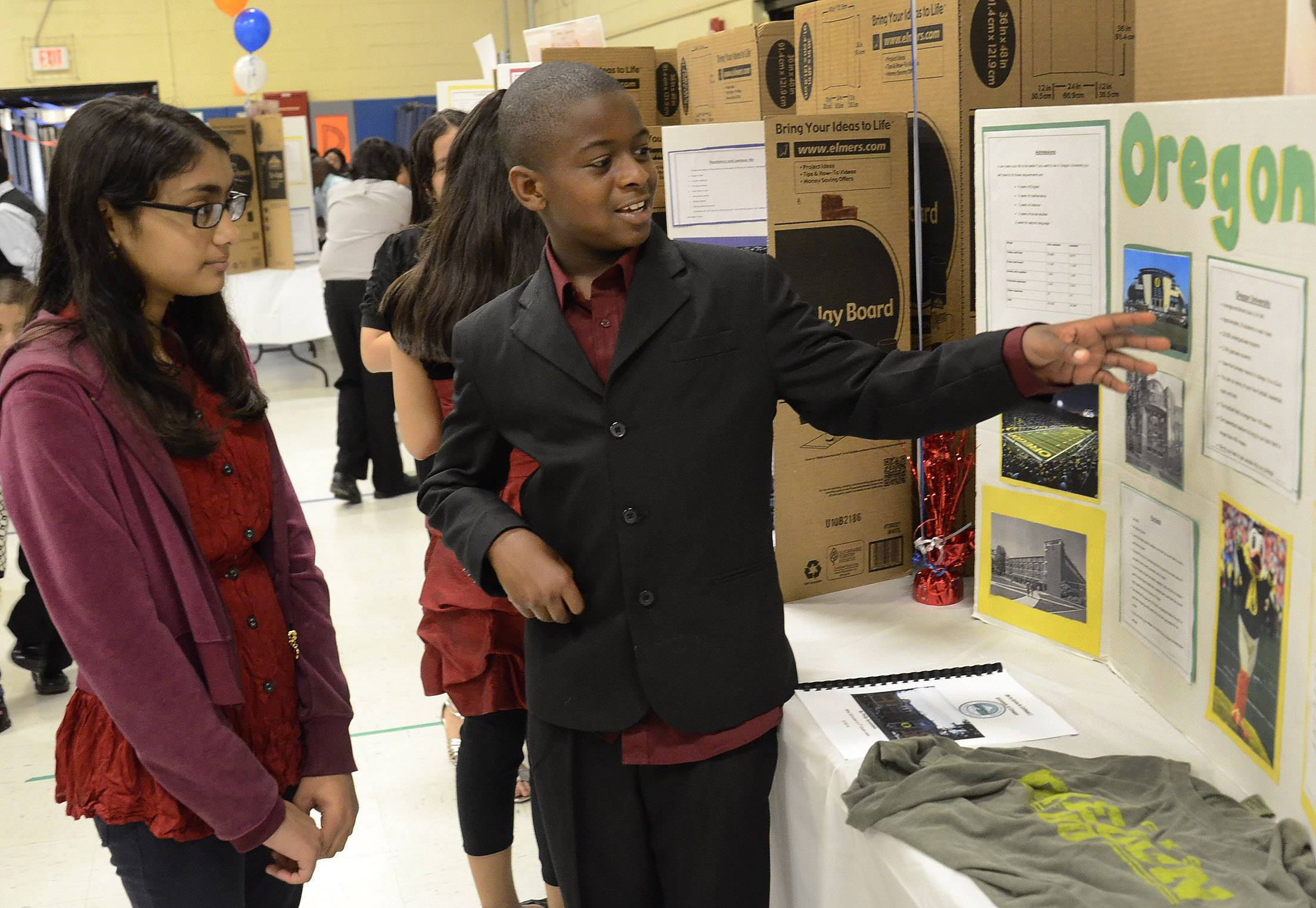 Philip Ayomidele explains the finer points of the University of Oregon to Diya Sonani, left, during the college fair Friday at Ontarioville Elementary.