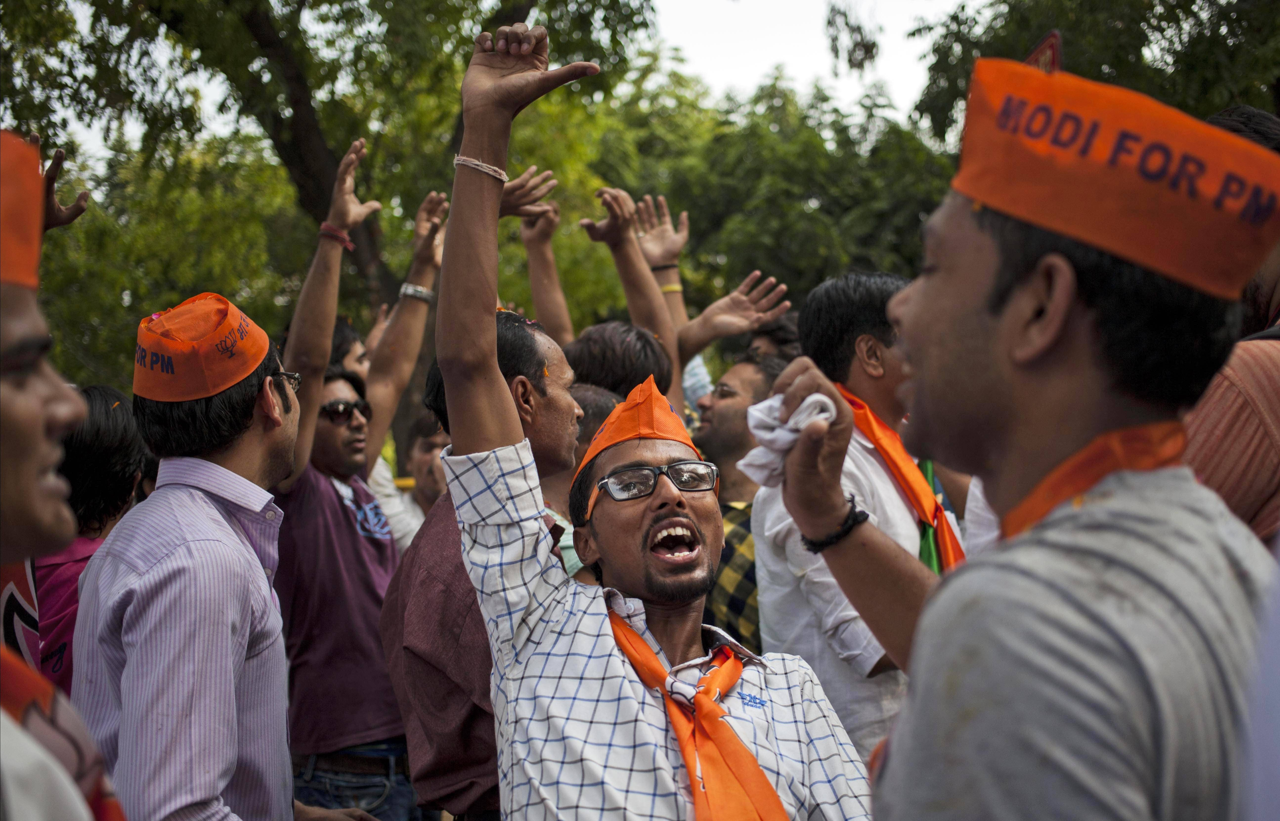 Bharatiya Janata Party (BJP) supporters dance to celebrate election results that showed the BJP winning by a landslide, outside the party headquarters in New Delhi, India, Friday, May 16, 2014.