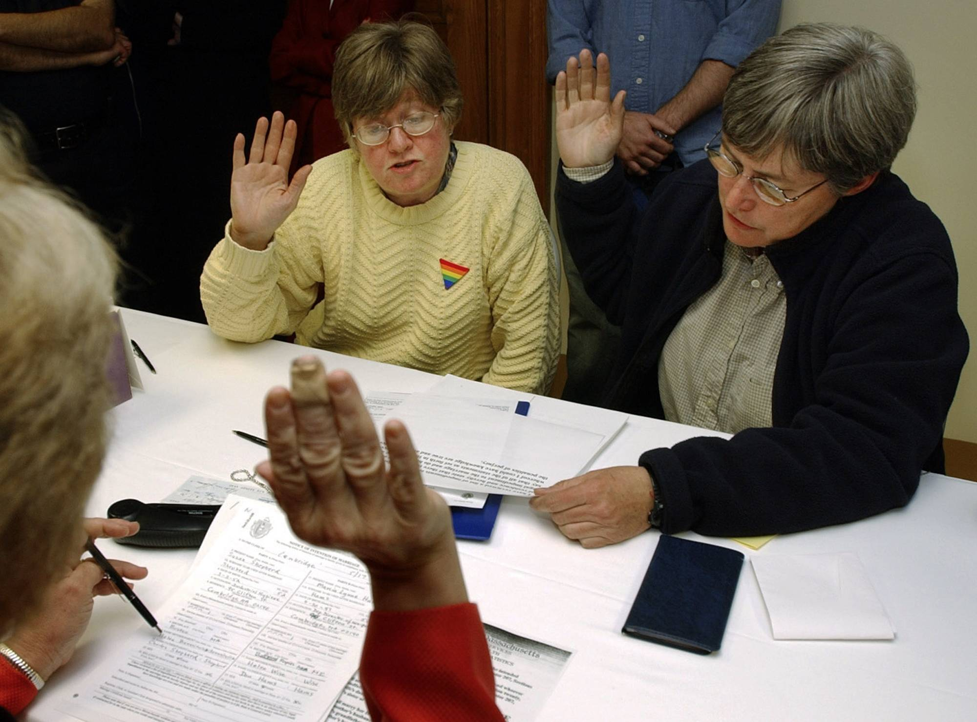 Marcia Hams, left, and her partner, Susan Shepherd, right, take an oath administered by City Clerk D. Margaret Drury, foreground, during the application process for a marriage license in 2004. Hams and Shepherd were the first couple to complete the application process as Massachusetts became the first state to legalize same-sex marriage in the United States, and were wed later that day.