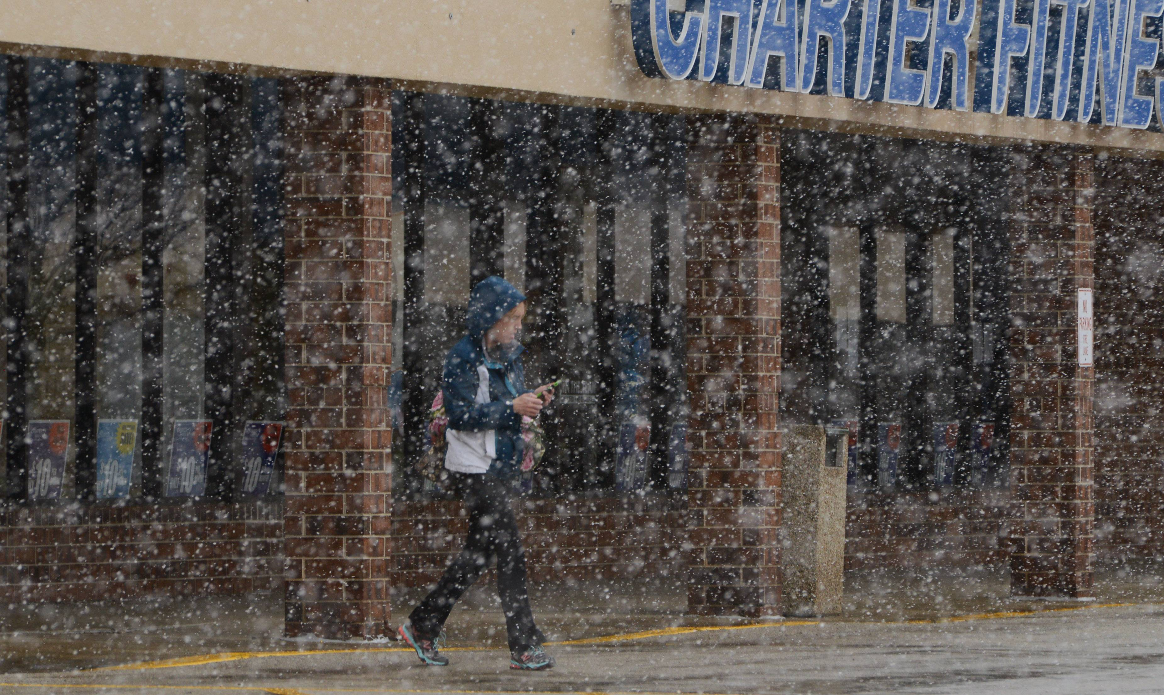 A Crystal Lake Charter Fitness member heads out into a flurry of snow Friday morning.